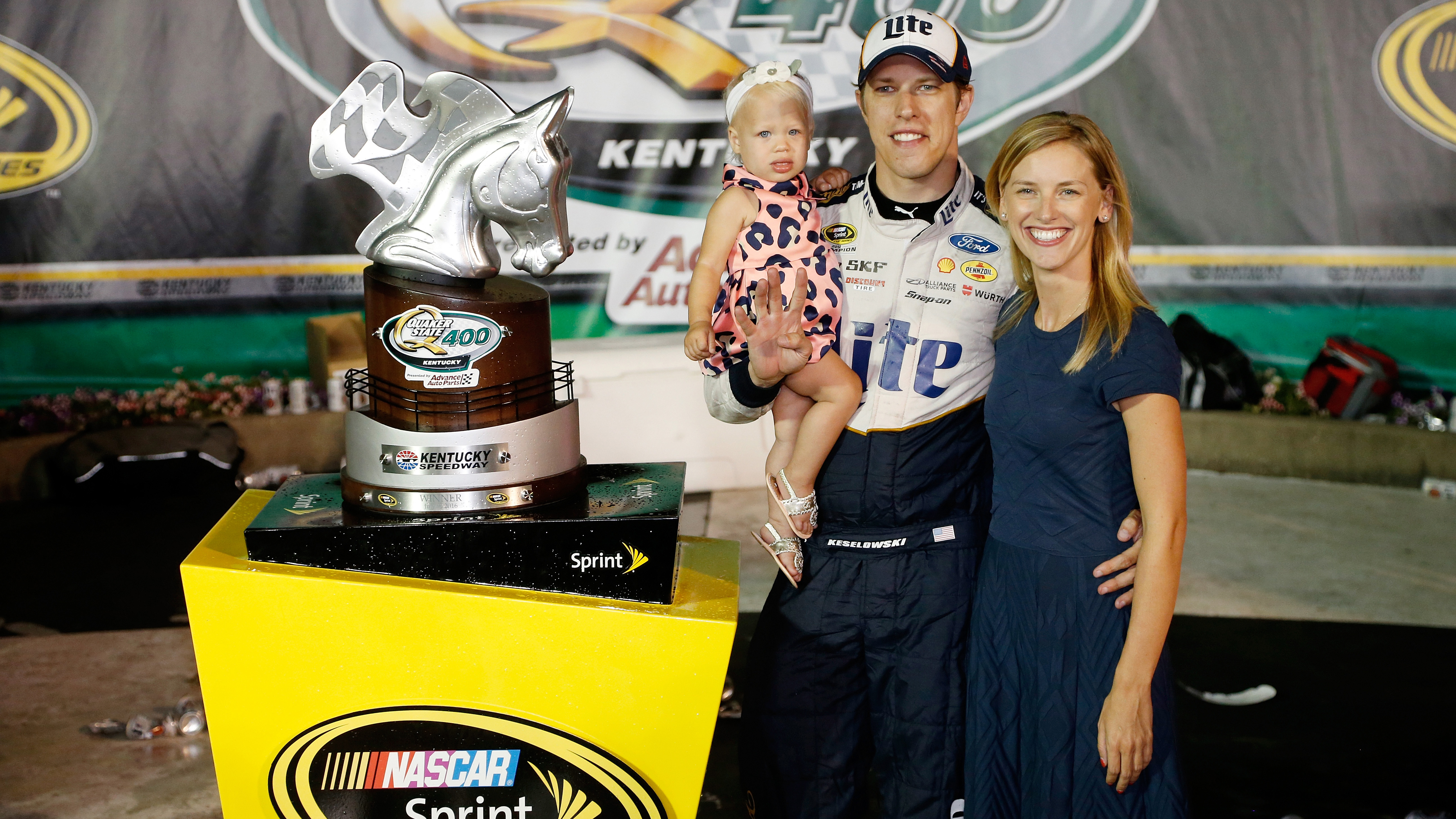 SPARTA, KY - JULY 09:  Brad Keselowski, driver of the #2 Miller Lite Ford, poses in Victory Lane with his girlfriend, Paige White, and daughter, Scarlett, after winning the NASCAR Sprint Cup Series Quaker State 400 at Kentucky Speedway on July 9, 2016 in Sparta, Kentucky.  (Photo by Brian Lawdermilk/NASCAR via Getty Images)