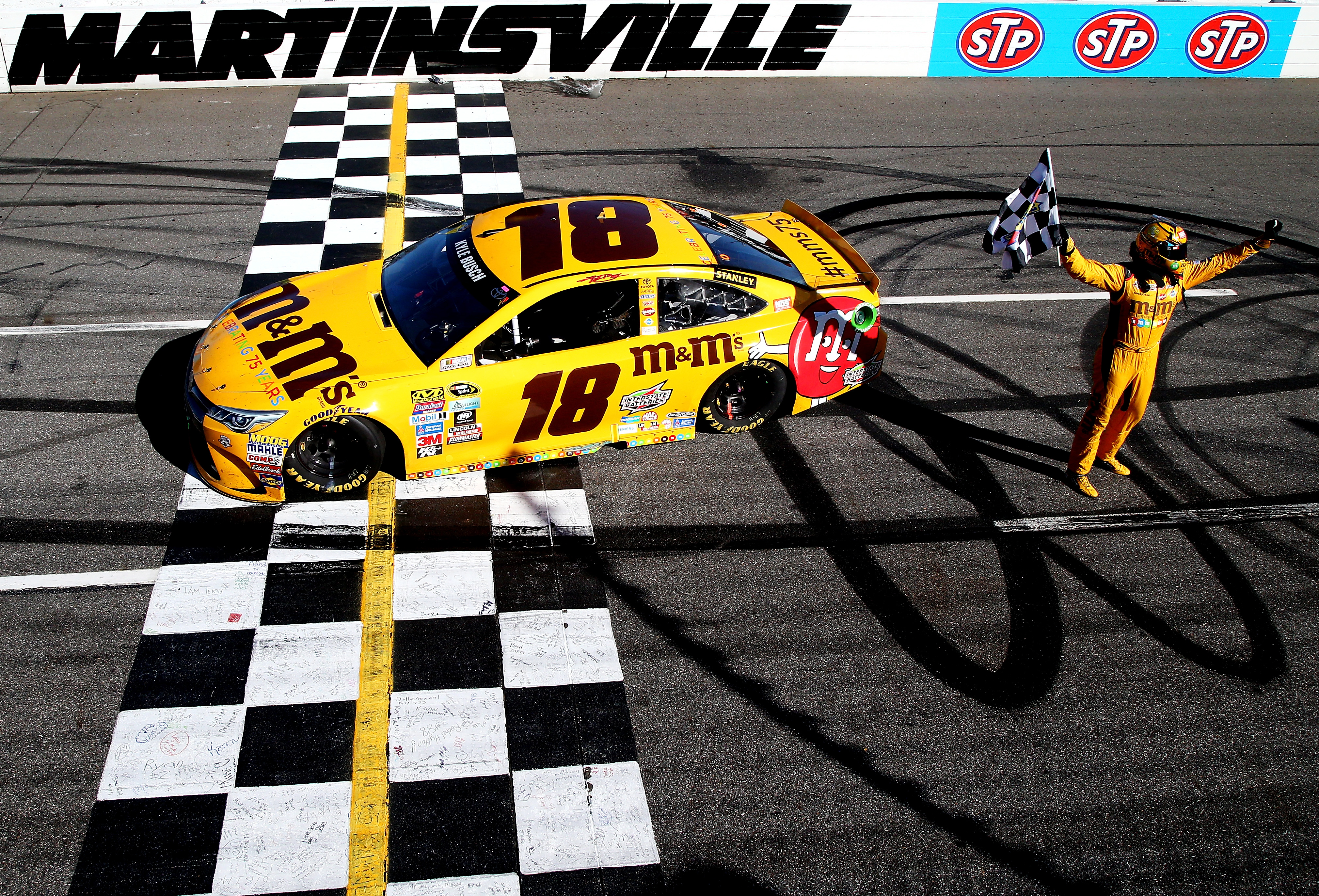 MARTINSVILLE, VA - APRIL 03:  Kyle Busch, driver of the #18 M&M's 75th Anniversary Toyota, celebrates with the checkered flag after winning the NASCAR Sprint Cup Series STP 500 at Martinsville Speedway on April 3, 2016 in Martinsville, Virginia.  (Photo by Sean Gardner/NASCAR via Getty Images)