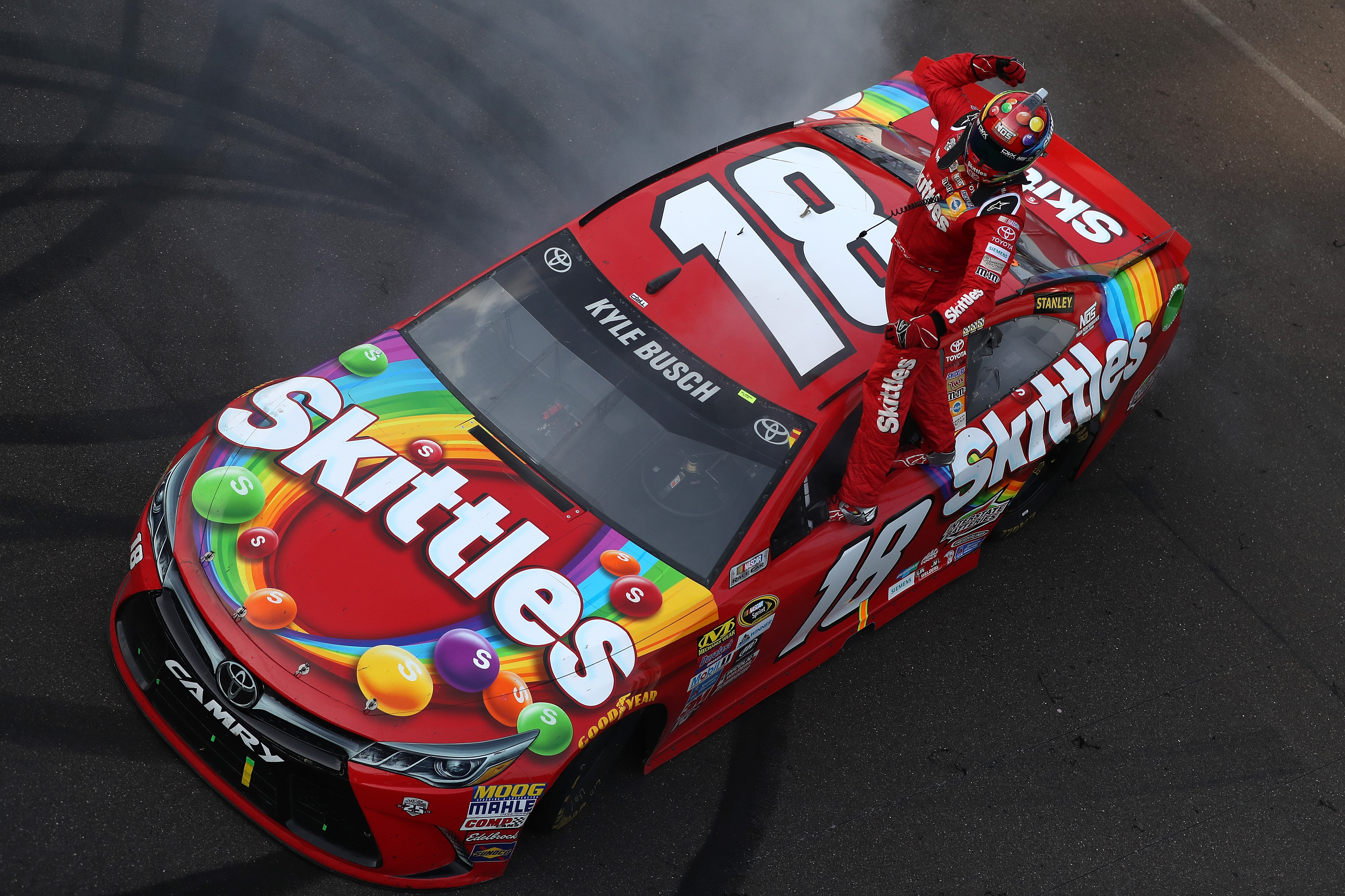 INDIANAPOLIS, IN - JULY 24: Kyle Busch, driver of the #18 Skittles Toyota, celebrates winning the NASCAR Sprint Cup Series Crown Royal Presents the Combat Wounded Coalition 400 at Indianapolis Motor Speedway on July 24, 2016 in Indianapolis, Indiana. (Photo by Sean Gardner/NASCAR via Getty Images)