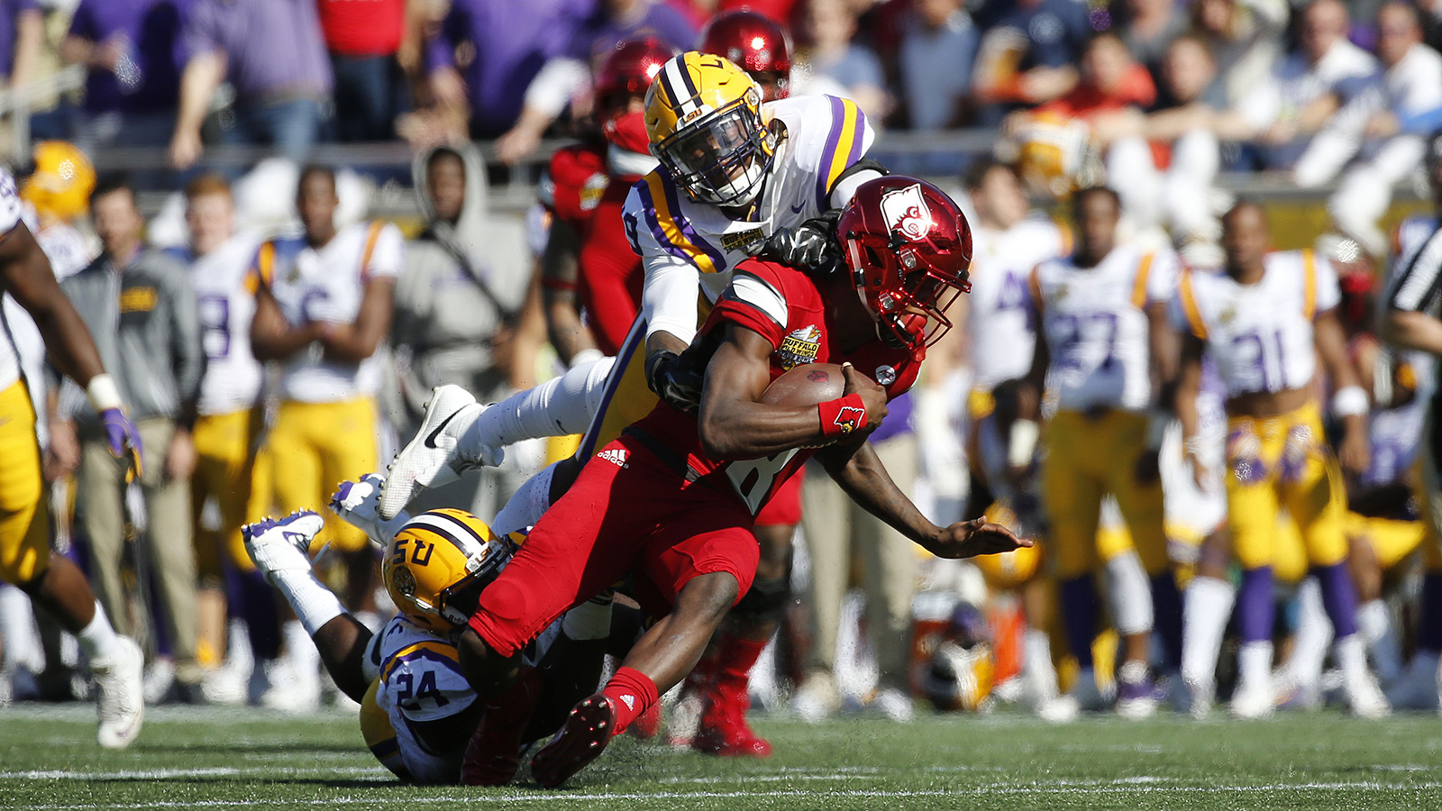 Dec 31, 2016; Orlando, FL, USA; Louisville Cardinals quarterback Lamar Jackson (8) runs with the ball as LSU Tigers defensive end Arden Key (49) tackles  during the first half at Camping World Stadium. Mandatory Credit: Kim Klement-USA TODAY Sports