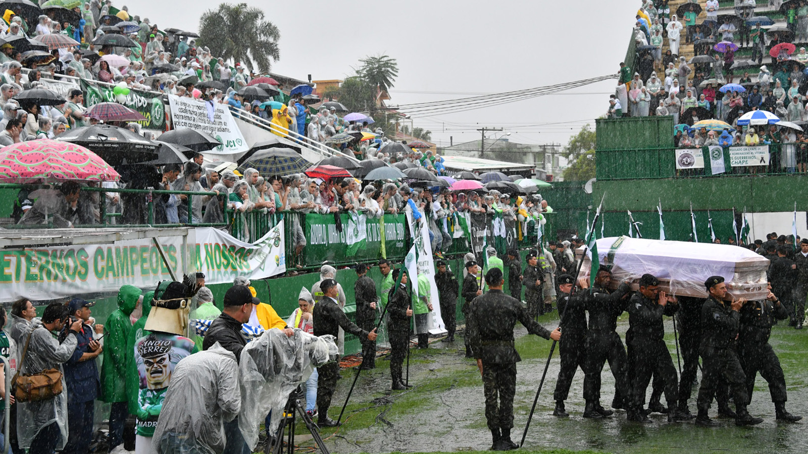 Soldiers carry into the stadium under heavy rain the coffins of the members of the Chapecoense Real football club team killed in a plane crash in Colombia, in  Chapeco, Santa Catarina, southern Brazil, on December 3, 2016.  The bodies of 50 players, coaches and staff from a Brazilian football team tragically wiped out in a plane crash in Colombia arrived home Saturday for a massive funeral. / AFP / Nelson Almeida        (Photo credit should read NELSON ALMEIDA/AFP/Getty Images)