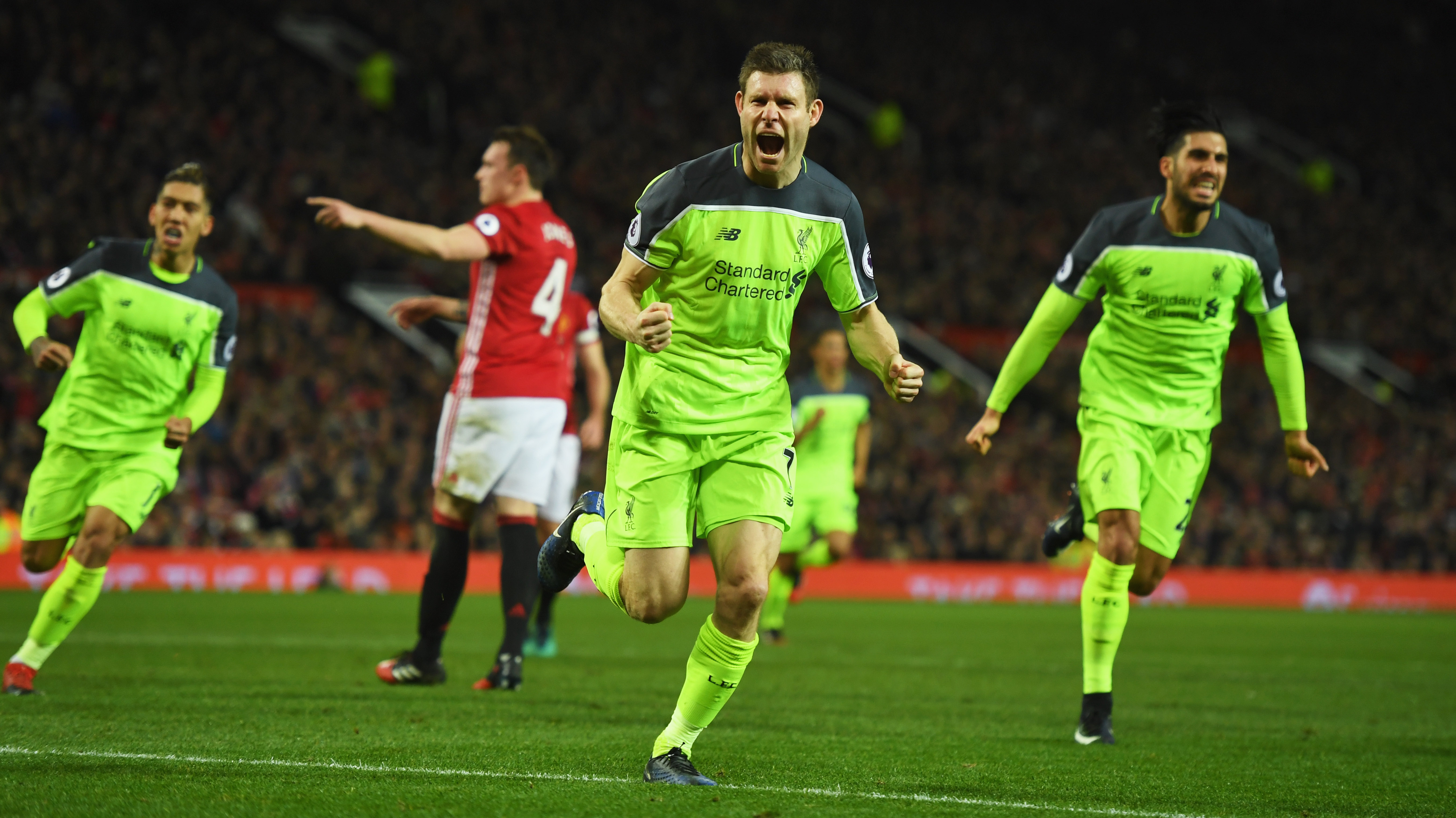 MANCHESTER, ENGLAND - JANUARY 15:  James Milner of Liverpool (C) celebrates as he scores their first goal from a penalty during the Premier League match between Manchester United and Liverpool at Old Trafford on January 15, 2017 in Manchester, England.  (Photo by Mike Hewitt/Getty Images)