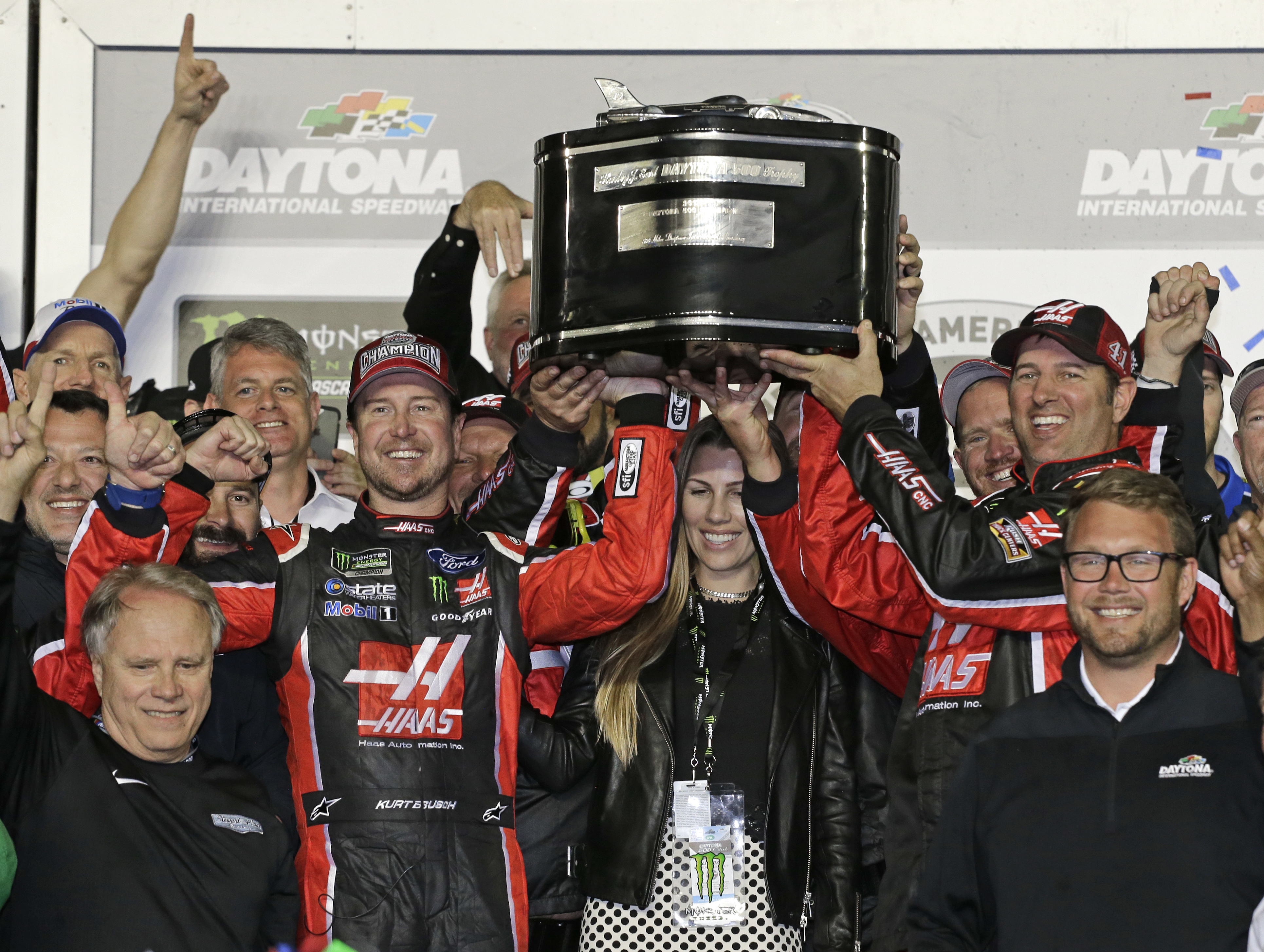 Kurt Busch, center left, and team members raise the trophy in Victory Lane after winning the NASCAR Daytona 500 auto race at Daytona International Speedway in Daytona Beach, Fla., Sunday, Feb. 26, 2017. (AP Photo/Terry Renna)