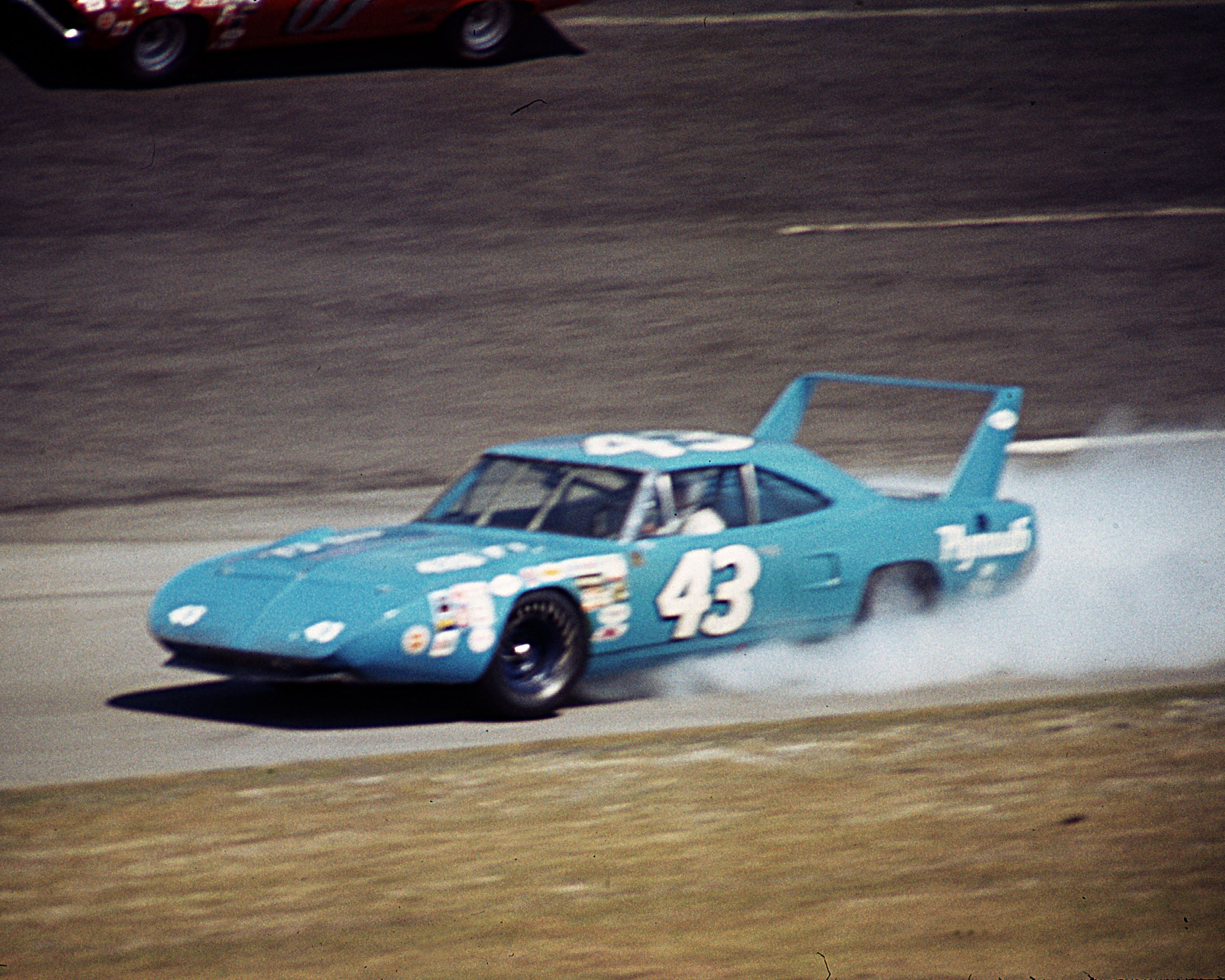 DAYTONA BEACH, FL — February 22, 1970:  Richard Petty hangs on to his winged Plymouth Superbird as the engine blows up on lap seven of the Daytona 500 NASCAR Cup race.  Although Petty was scored in next-to-last position (39th), his teammate Pete Hamilton went on to score the victory.  (Photo by ISC Images & Archives via Getty Images)