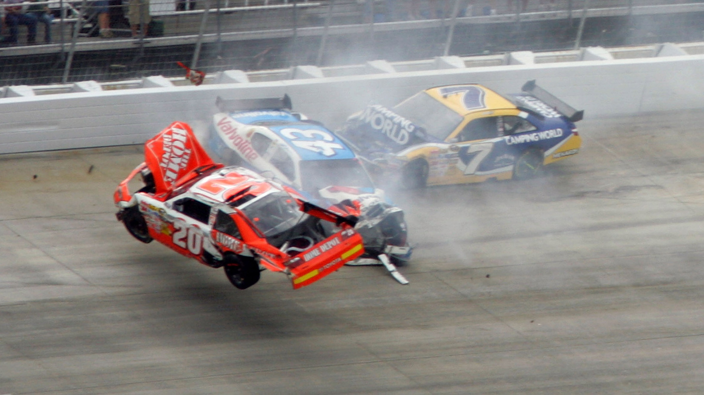 DOVER, DE - SEPTEMBER 27:  (L-R) Joey Logano, driver of the #20 Home Depot Toyota, flips his car after he was involved in a wreck with Reed Sorenson, driver of the #43 Valvoline Dodge, Robby Gordon, driver of the #7 Camping World Toyota and Martin Truex Jr. (not pictured), driver of the #1 Vaseline MEN Body Lotion Chevrolet during the NASCAR Sprint Cup Series AAA 400 at Dover International Speedway on September 27, 2009 in Dover, Delaware.  (Photo by Jerry Markland/Getty Images for NASCAR)