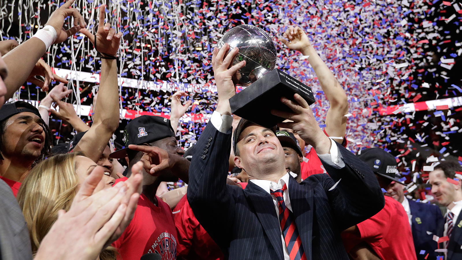 Arizona coach Sean Miller holds up the trophy after Arizona defeated Oregon 83-80 in an NCAA college basketball game for the championship of the Pac-12 men's tournament Saturday, March 11, 2017, in Las Vegas. (AP Photo/John Locher)