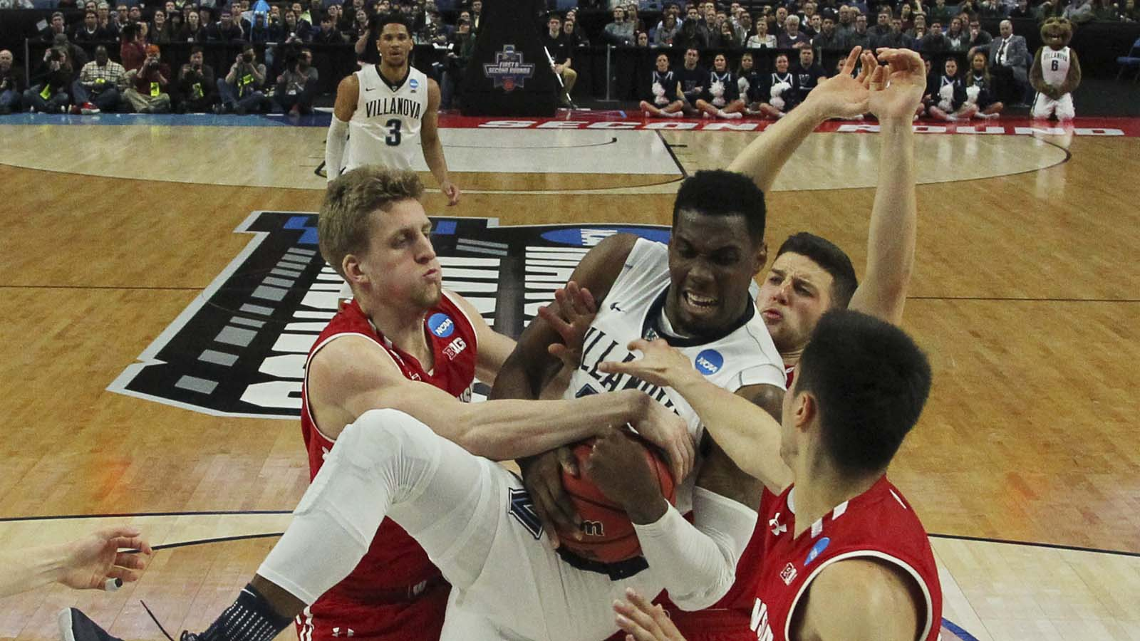 Villanova forward Darryl Reynolds grabs a rebound against Wisconsin guard Brevin Pritzl (left), guard Zak Showalter (center) and guard Bronson Koenig (right) during the first half of a second-round men's college basketball game in the NCAA Tournament, Sat