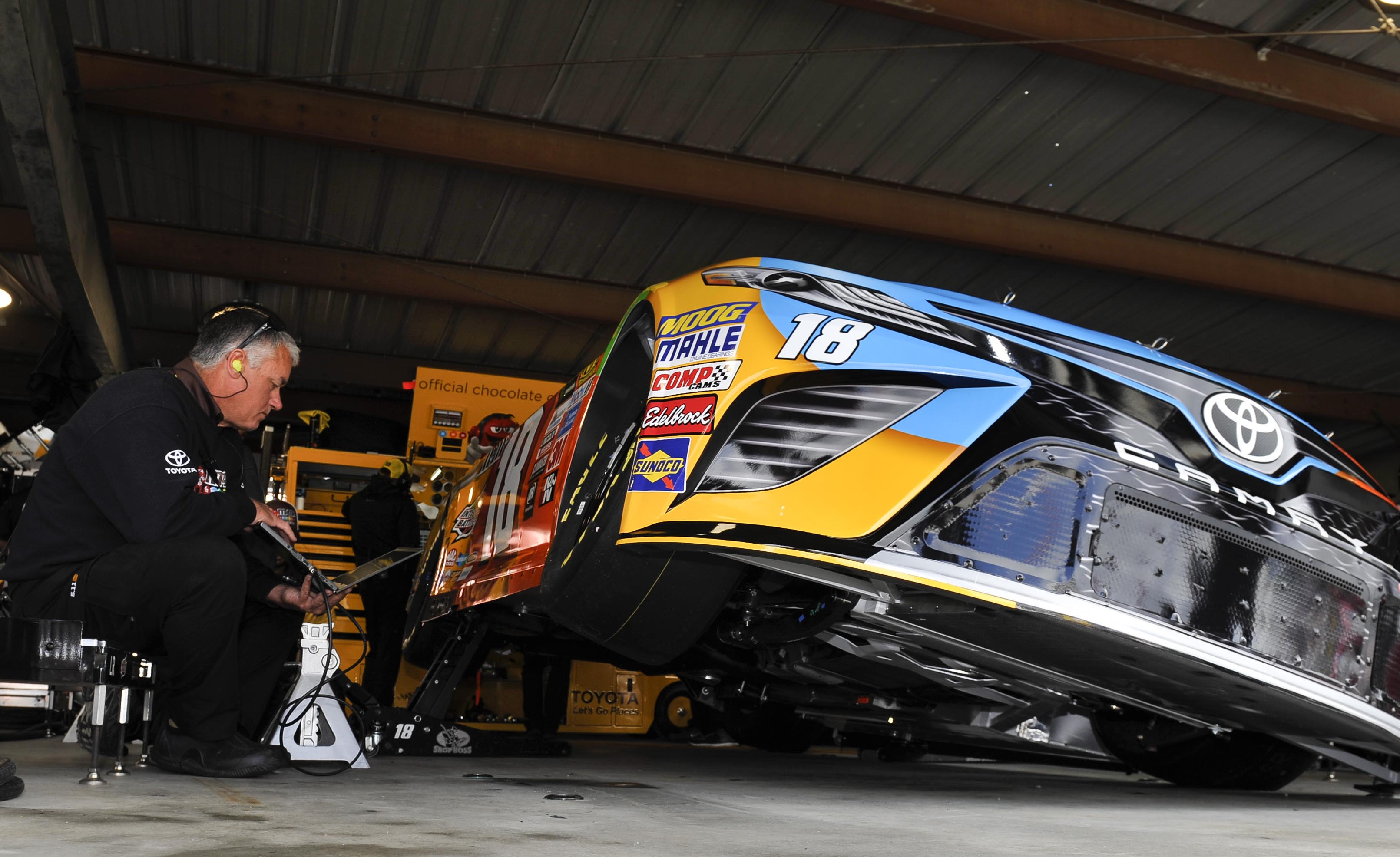 Mar 31, 2017; Martinsville, VA, USA; A crew member for NASCAR Cup Series driver Kyle Busch (18) checks a tire reading during practice for the STP 500 at Martinsville Speedway. Mandatory Credit: Michael Shroyer-USA TODAY Sports