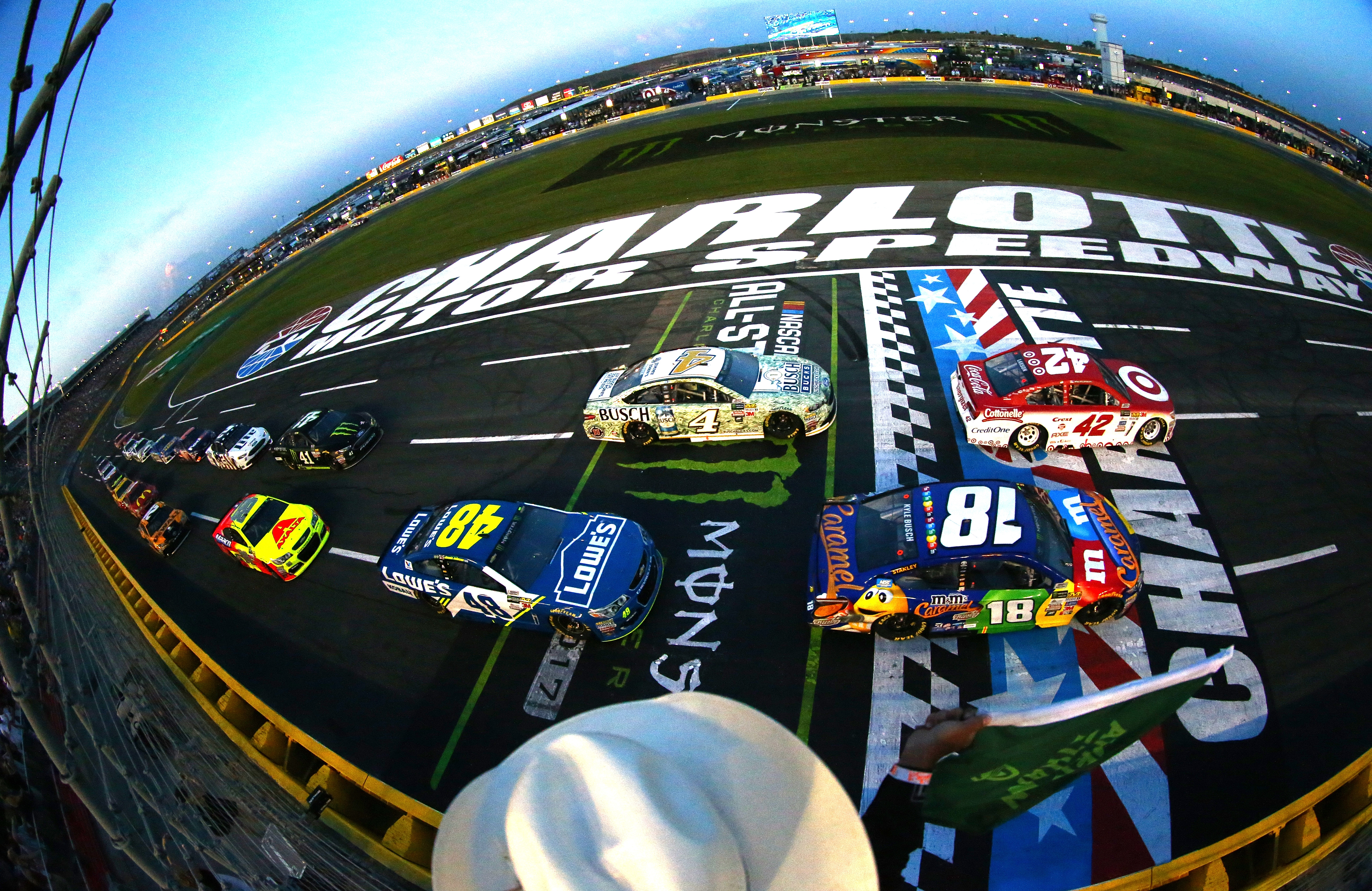 CHARLOTTE, NC - MAY 20:  Kyle Larson, driver of the #42 Target Chevrolet, and Kyle Busch, driver of the #18 M&M's Caramel Toyota, take the green flag to start the Monster Energy NASCAR All Star Race at Charlotte Motor Speedway on May 20, 2017 in Charlotte, North Carolina.  (Photo by Sarah Crabill/Getty Images)