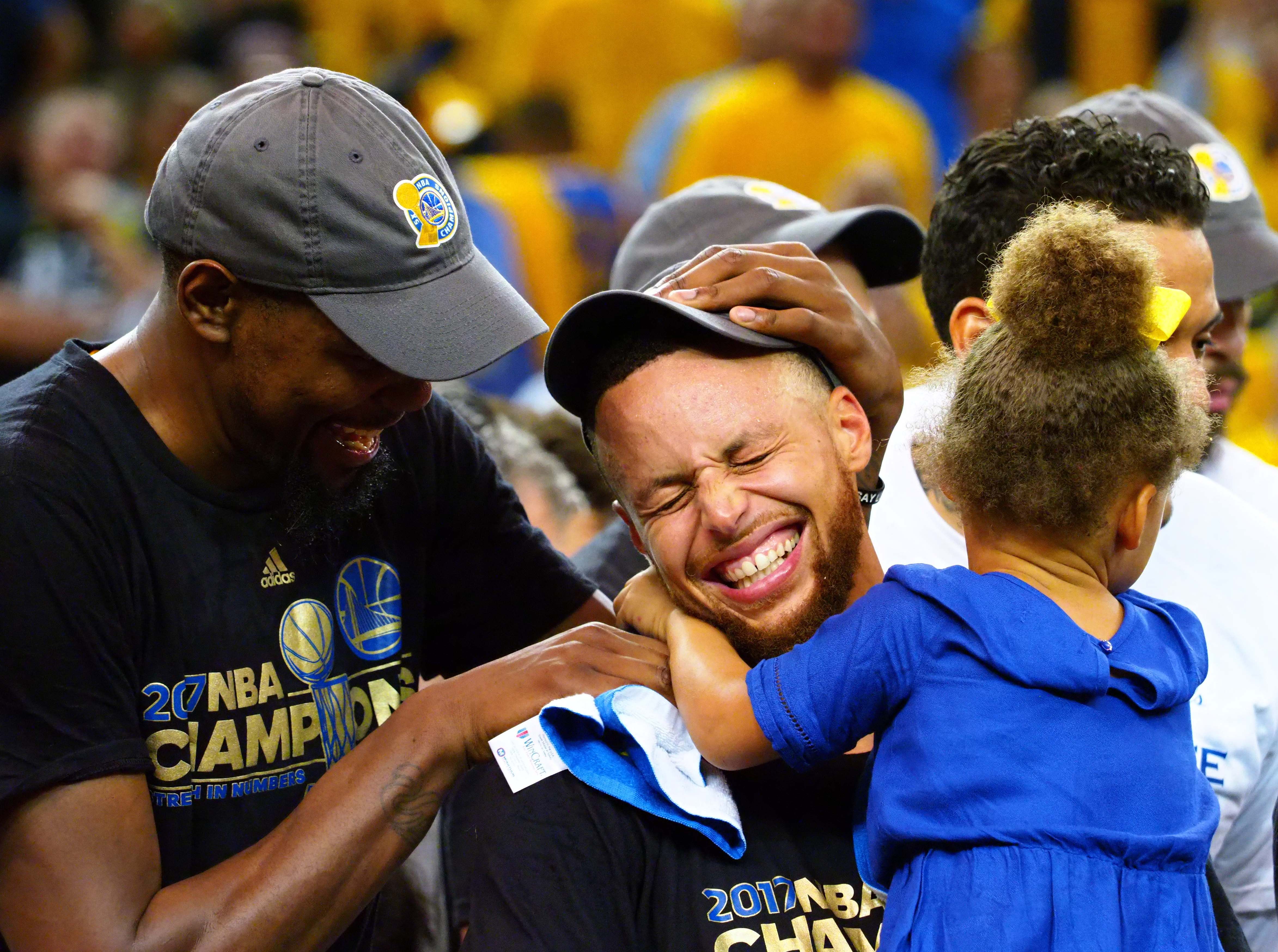 Jun 12, 2017; Oakland, CA, USA; Golden State Warriors forward Kevin Durant (35), guard Stephen Curry (30) celebrate with his caught Riley in game five of the 2017 NBA Finals at Oracle Arena. Mandatory Credit: Kelley L Cox-USA TODAY Sports