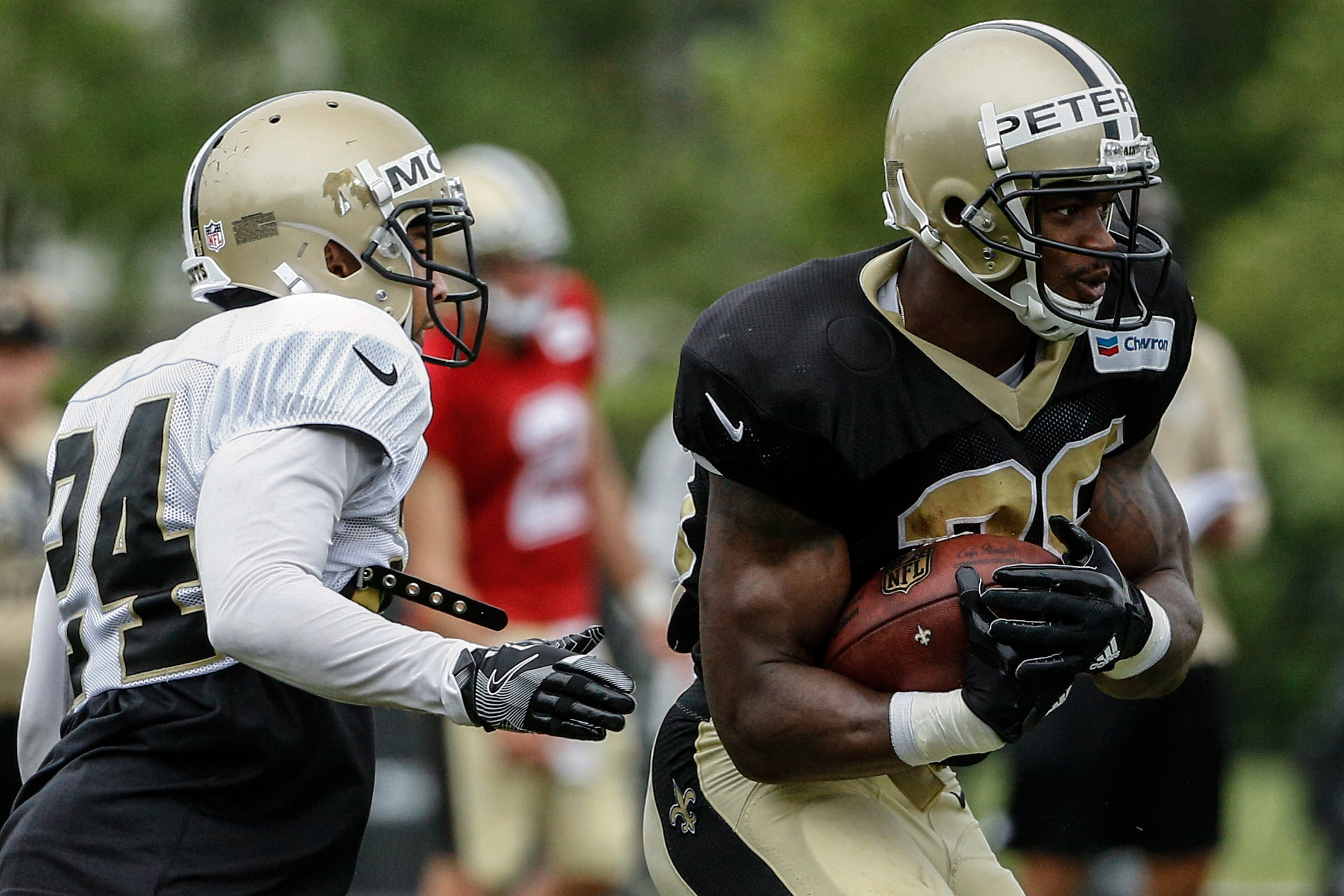 Jul 29, 2017; Metairie, LA, USA; New Orleans Saints running back Adrian Peterson (28) breaks a tackle by corner back Sterling Moore (24) during training camp at the Metairie Training Facility. Mandatory Credit: Derick E. Hingle-USA TODAY Sports
