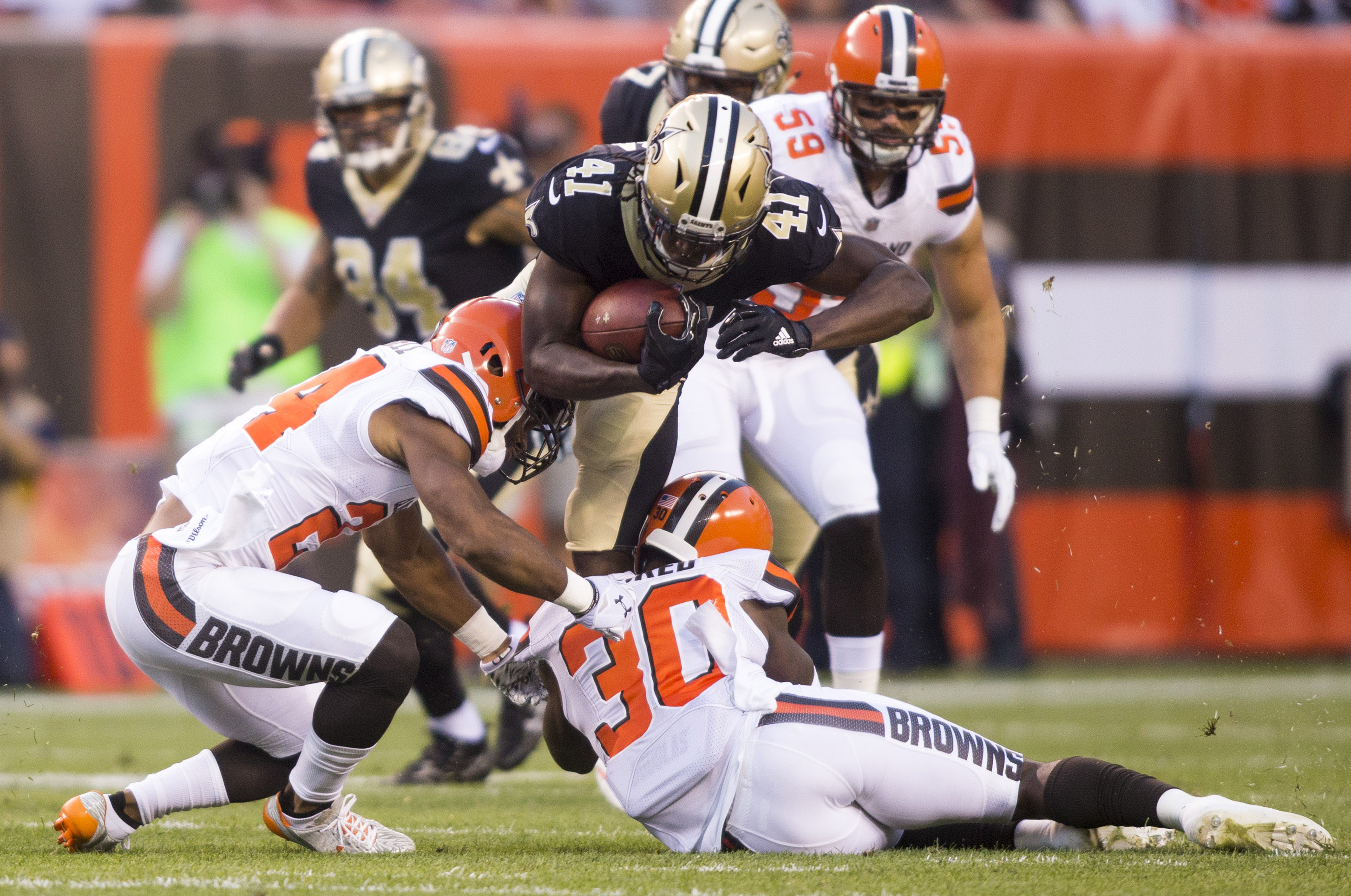 Aug 10, 2017; Cleveland, OH, USA; New Orleans Saints running back Alvin Kamara (41) gets tackled by Cleveland Browns strong safety Ibraheim Campbell (24) and strong safety Derrick Kindred (30) at FirstEnergy Stadium. Campbell was injured on the play.  Mandatory Credit: Scott R. Galvin-USA TODAY Sports