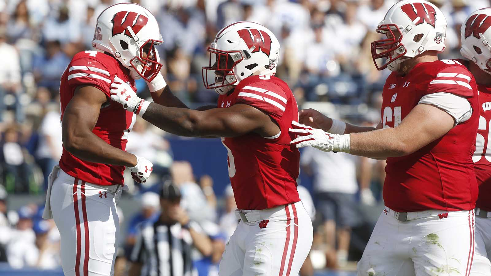 Wisconsin wide receiver A.J. Taylor, left, celebrates after scoring a touchdown with running back Chris James, center, and offensive lineman Tyler Biadasz (61) in the second half during an NCAA college football game against BYU, Saturday, Sept. 16, 2017, in Provo, Utah. (AP Photo/Kim Raff)