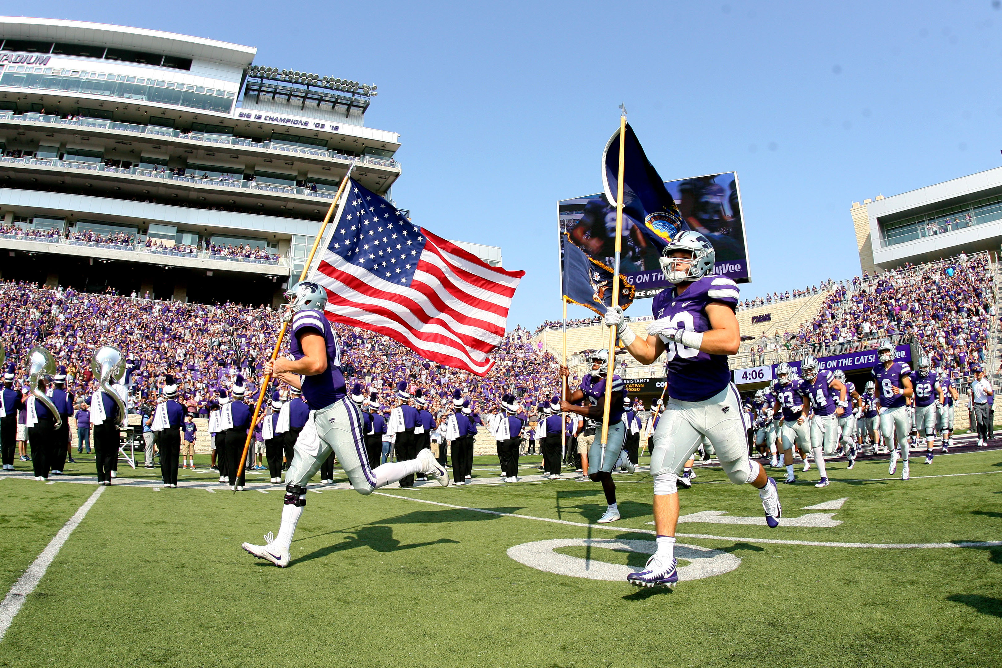 Sep 9, 2017; Manhattan, KS, USA; Kansas State Wildcats quarterback Jesse Ertz (16) and linebacker Trent Tanking (58) carry flags as they lead the Wildcats onto the field before the start of a game against the Charlotte 49ers at Bill Snyder Family Stadium. The Wildcats won 55-7. Mandatory Credit: Scott Sewell-USA TODAY Sports
