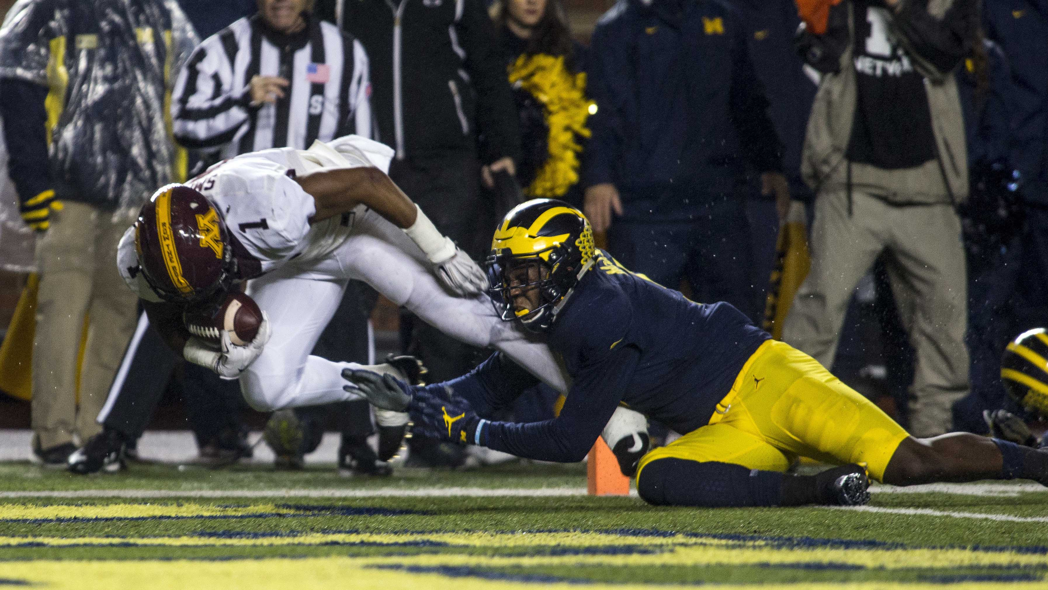 Minnesota running back Rodney Smith (1) scores a touchdown, defended by Michigan linebacker Mike McCray, right, in the first quarter of an NCAA college football game in Ann Arbor, Mich., Saturday, Nov. 4, 2017. (AP Photo/Tony Ding)
