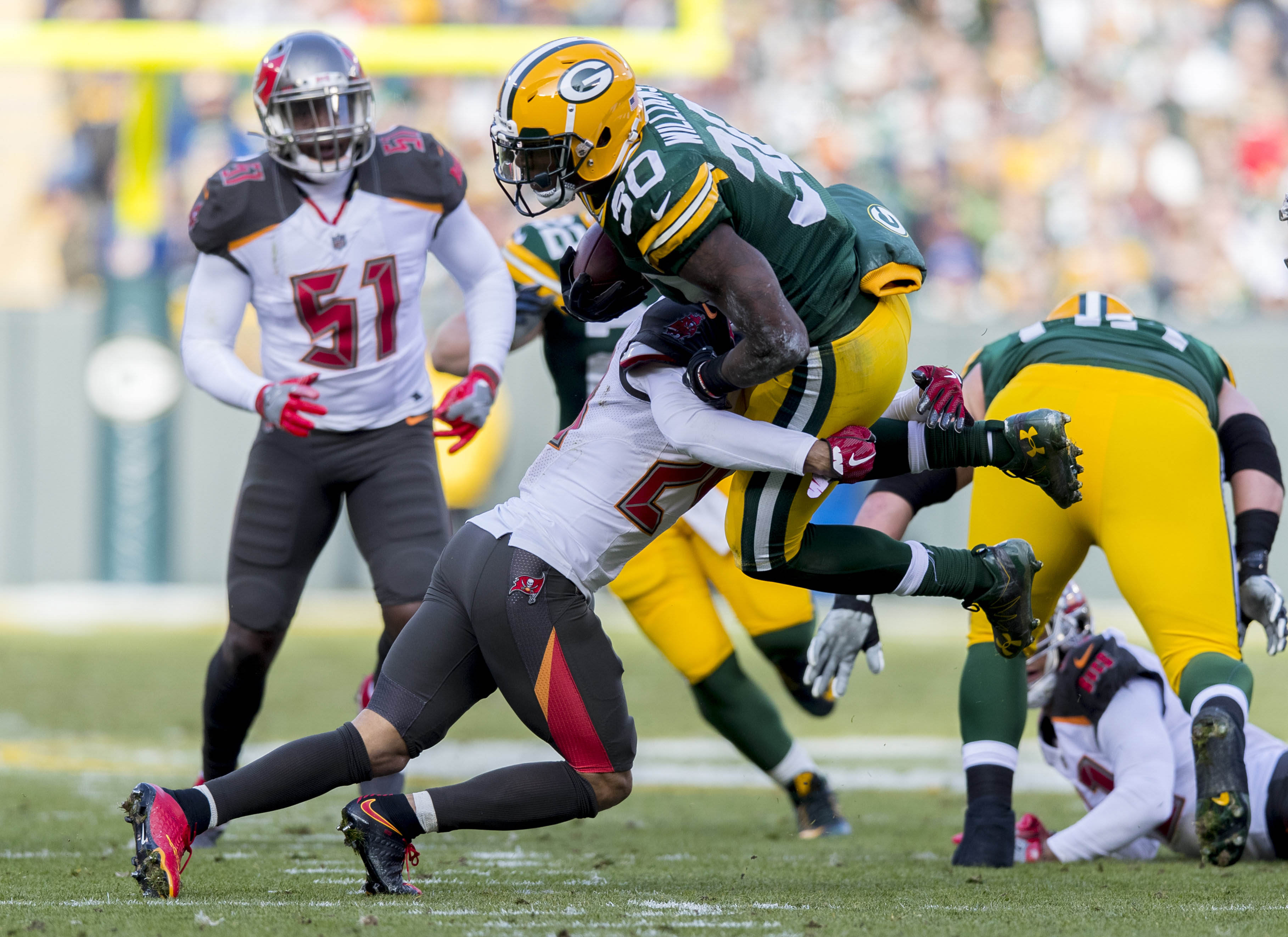 Dec 3, 2017; Green Bay, WI, USA; Green Bay Packers running back Jamaal Williams (30) is tackled with the football during the first quarter` against the Tampa Bay Buccaneers at Lambeau Field. Mandatory Credit: Jeff Hanisch-USA TODAY Sports
