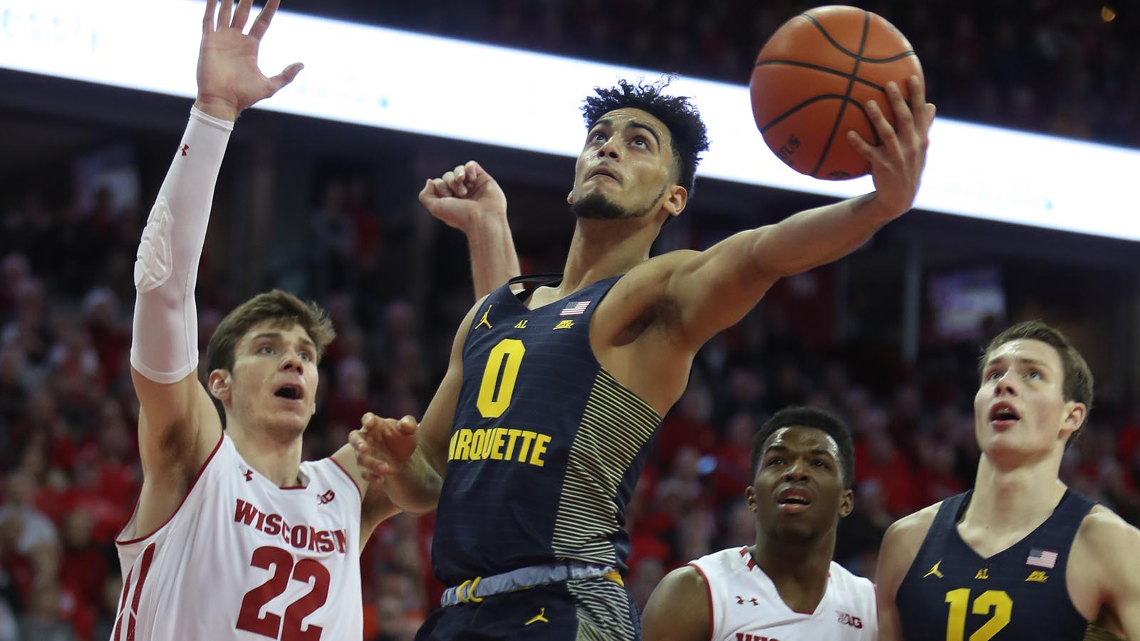 Dec 9, 2017; Madison, WI, USA; Marquette Golden Eagles guard Markus Howard (0) attempts a basket as Wisconsin Badgers forward Ethan Happ (22) looks on at the Kohl Center. Mandatory Credit: Mary Langenfeld-USA TODAY Sports