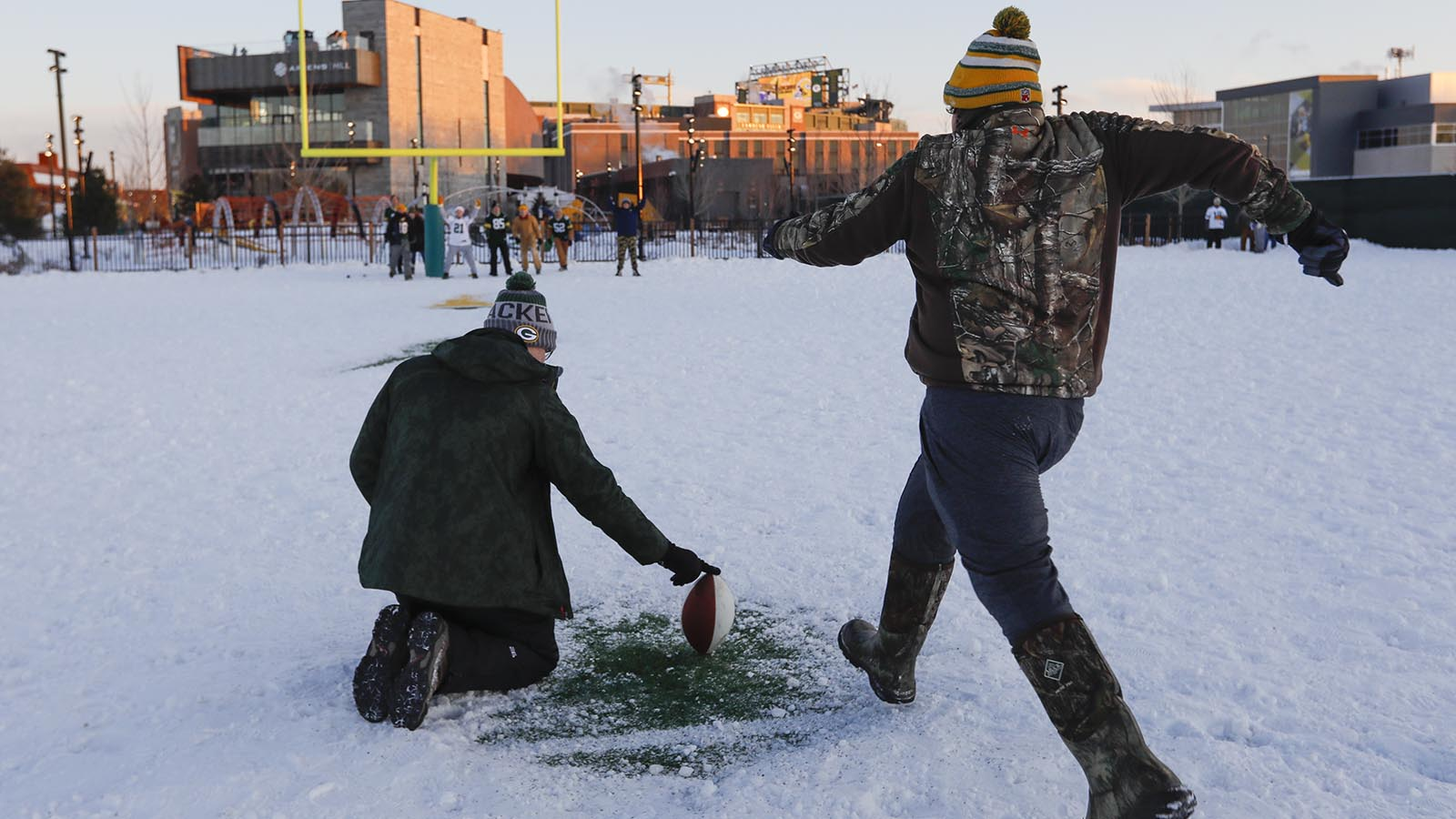 Fans play football near Lambeau Field before an NFL football game between the Green Bay Packers and the Minnesota Vikings Saturday, Dec. 23, 2017, in Green Bay, Wis. (AP Photo/Mike Roemer)