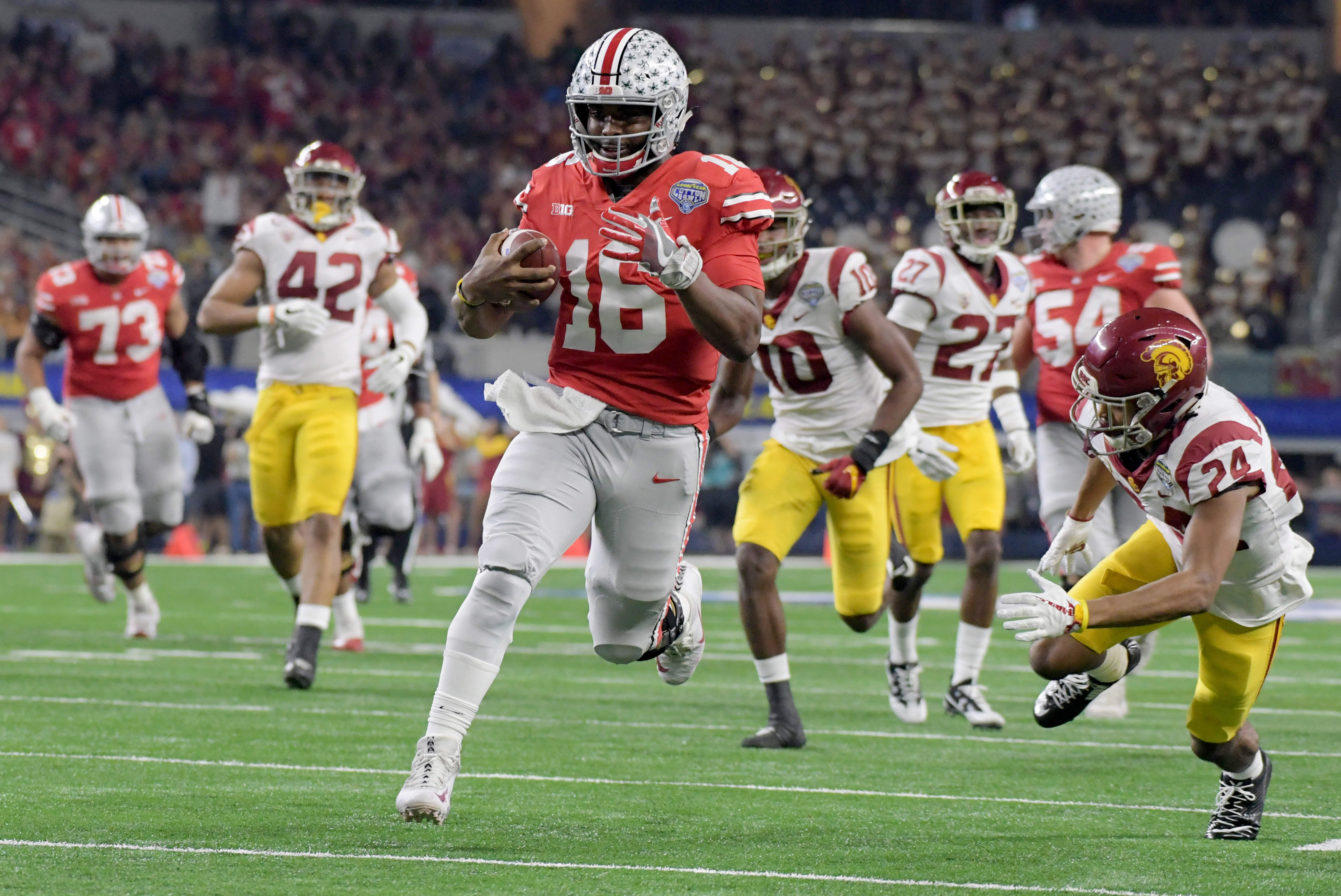 Dec 29, 2017; Arlington, TX, USA; Ohio State Buckeyes quarterback J.T. Barrett (16) runs in a touchdown past Southern California Trojans cornerback Isaiah Langley (24) in the 2017 Cotton Bowl at AT&T Stadium. Mandatory Credit: Kirby Lee-USA TODAY Sports