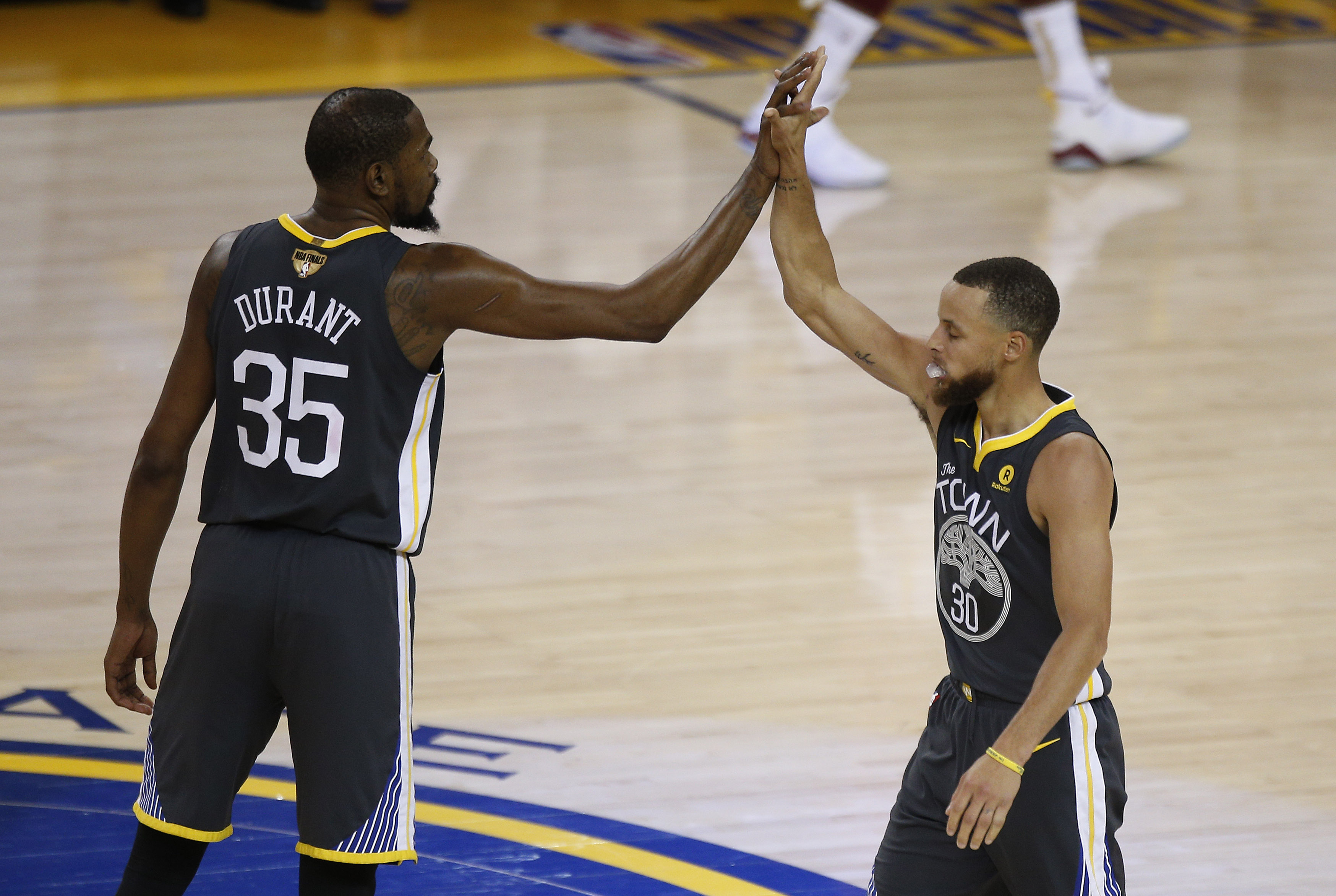 Jun 3, 2018; Oakland, CA, USA; Golden State Warriors guard Stephen Curry (30) reacts with forward Kevin Durant (35) after scoring a basket against the Cleveland Cavaliers during the first half in game two of the 2018 NBA Finals at Oracle Arena. Mandatory Credit: Cary Edmondson-USA TODAY Sports