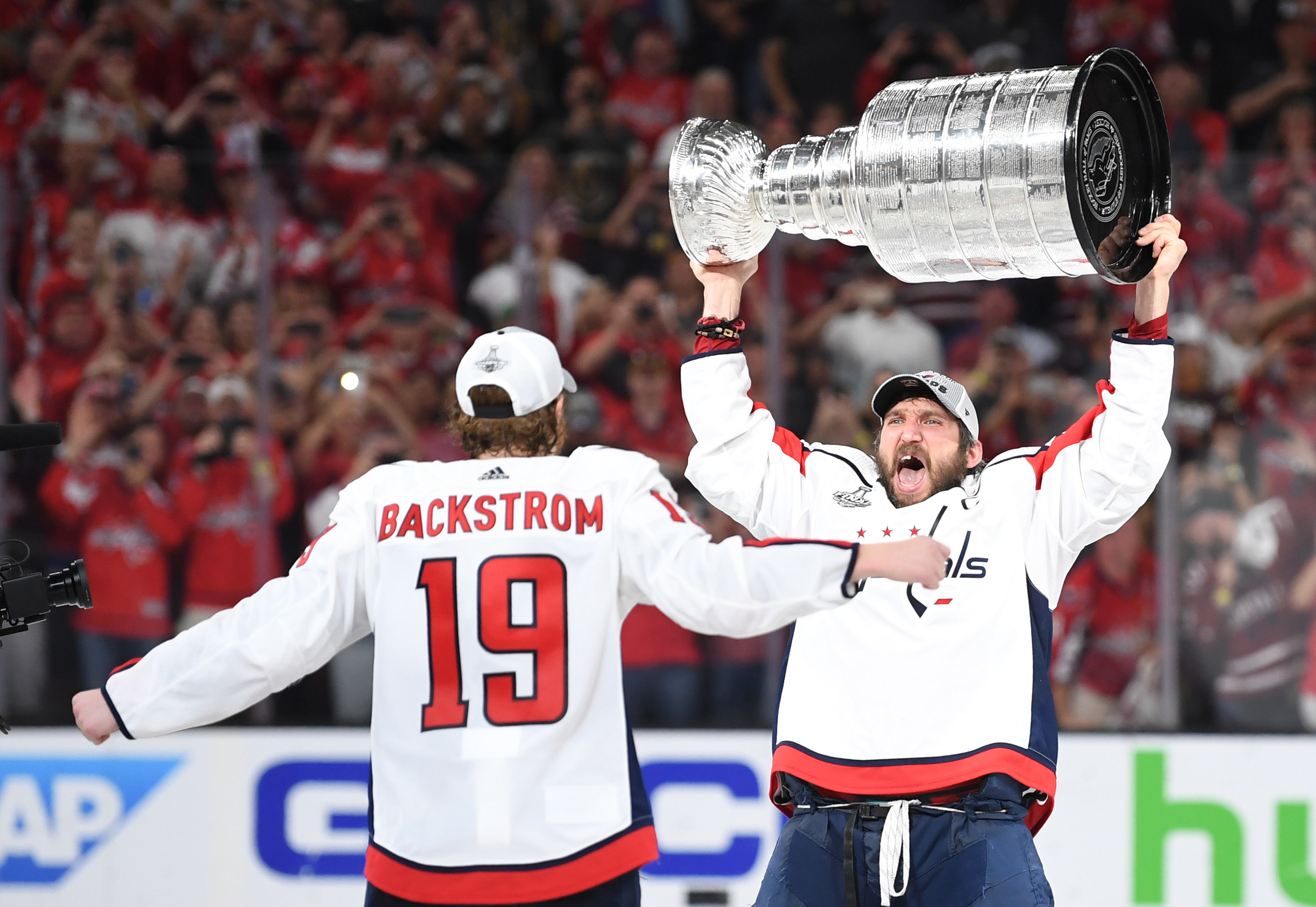Jun 7, 2018; Las Vegas, NV, USA; Washington Capitals left wing Alex Ovechkin (8) passes the Stanley Cup to center Nicklas Backstrom (19) after defeating the Vegas Golden Knights in game five of the 2018 Stanley Cup Final at T-Mobile Arena. Mandatory Credit: Stephen R. Sylvanie-USA TODAY Sports