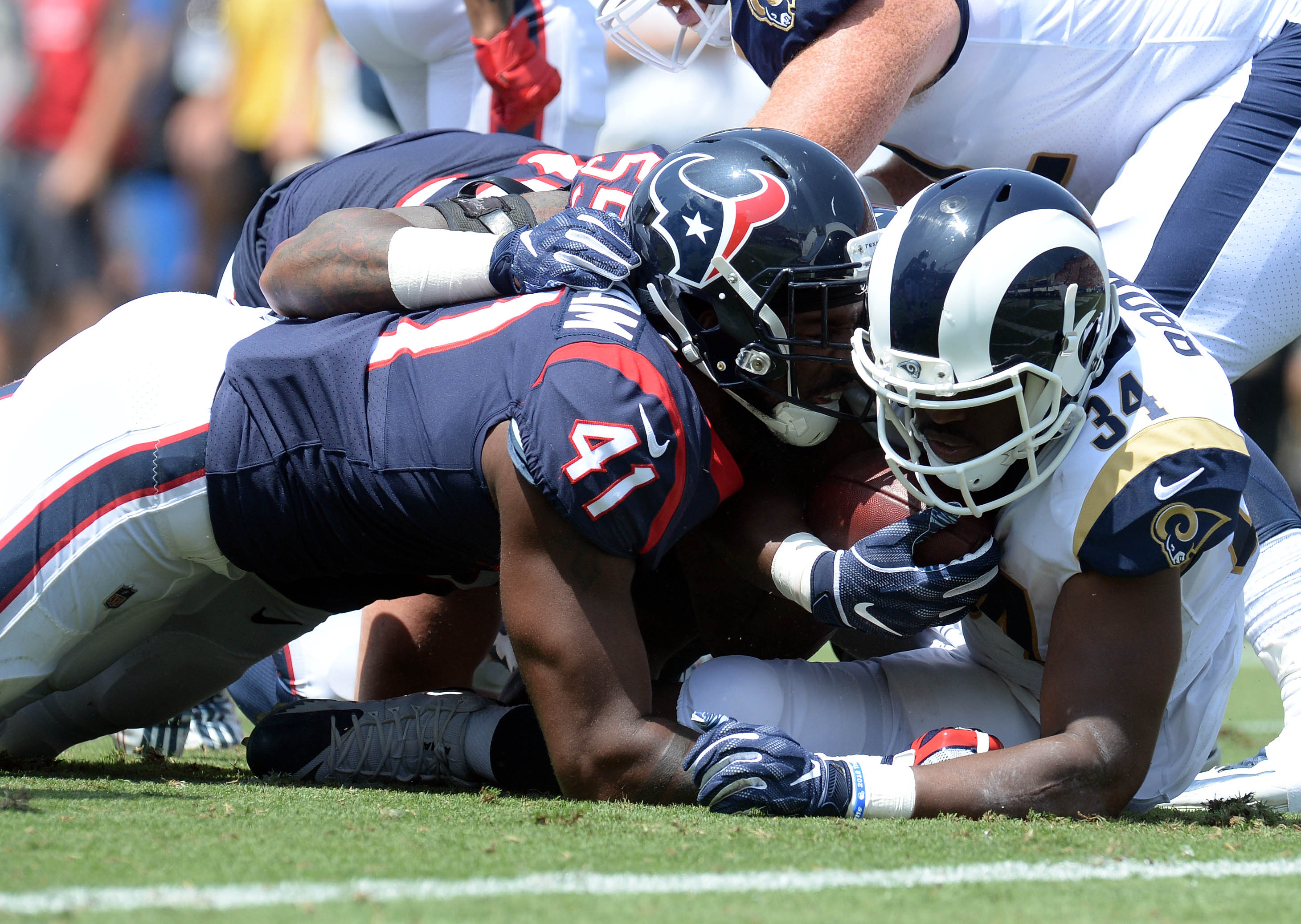 August 25, 2018; Los Angeles, CA, USA; Los Angeles Rams running back Malcolm Brown (34) is brought down by Houston Texans linebacker Zach Cunningham (41) during the first half at Los Angeles Memorial Coliseum. Mandatory Credit: Gary A. Vasquez-USA TODAY Sports