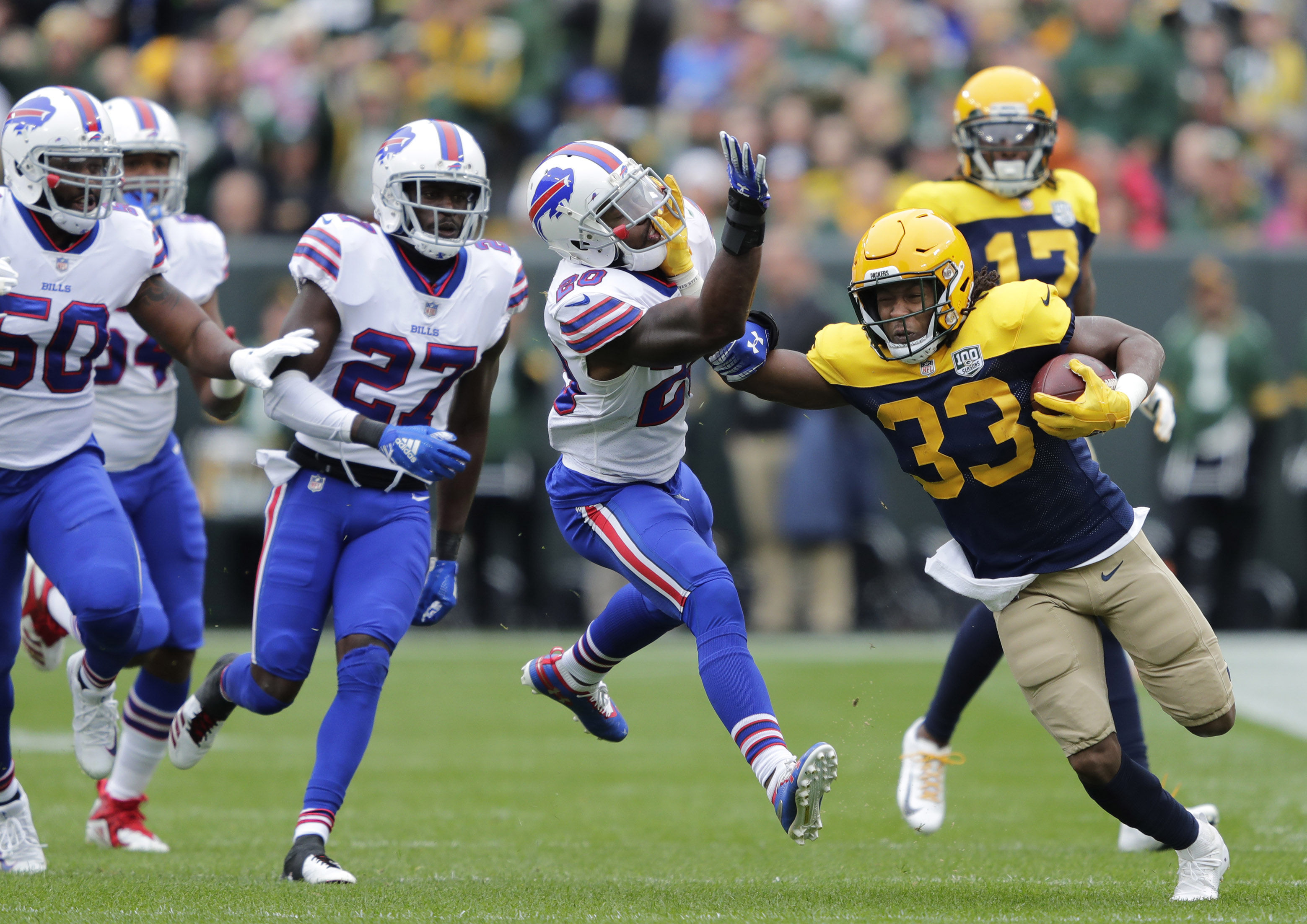 Sep 30, 2018; Green Bay, WI, USA; Green Bay Packers running back Aaron Jones (33) stiff arms Buffalo Bills defensive back Rafael Bush (20) during the first quarter at Lambeau Field. Dan Powers/Wisconsin via USA TODAY NETWORK