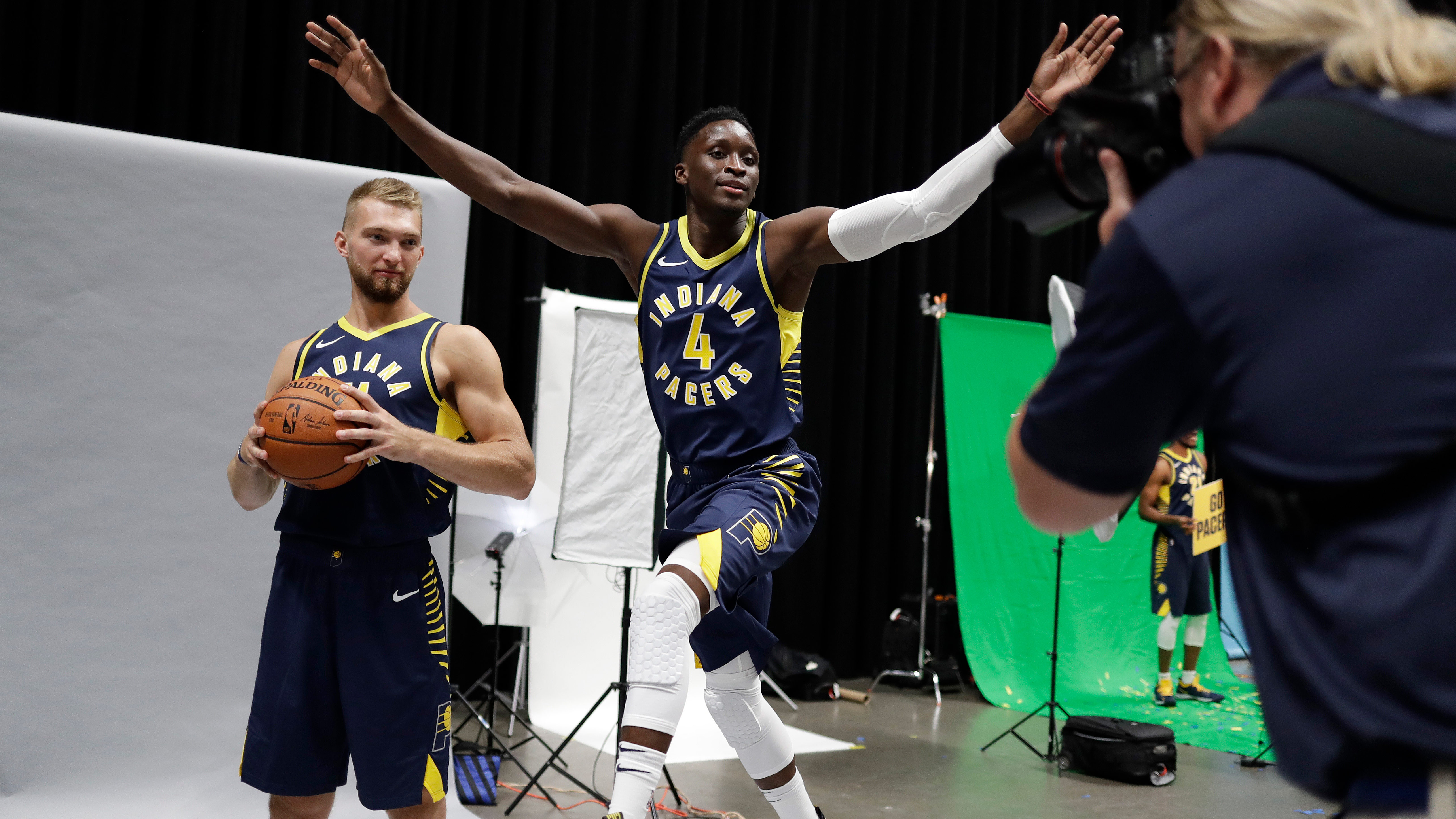 Indiana Pacers' Victor Oladipo (4) jumps into a photo of Domantas Sabonis that is being taken by Trevor Ruszkowski during media day at the NBA basketball team's practice facility, Monday, Sept. 24, 2018, in Indianapolis. (AP Photo/Darron Cummings)