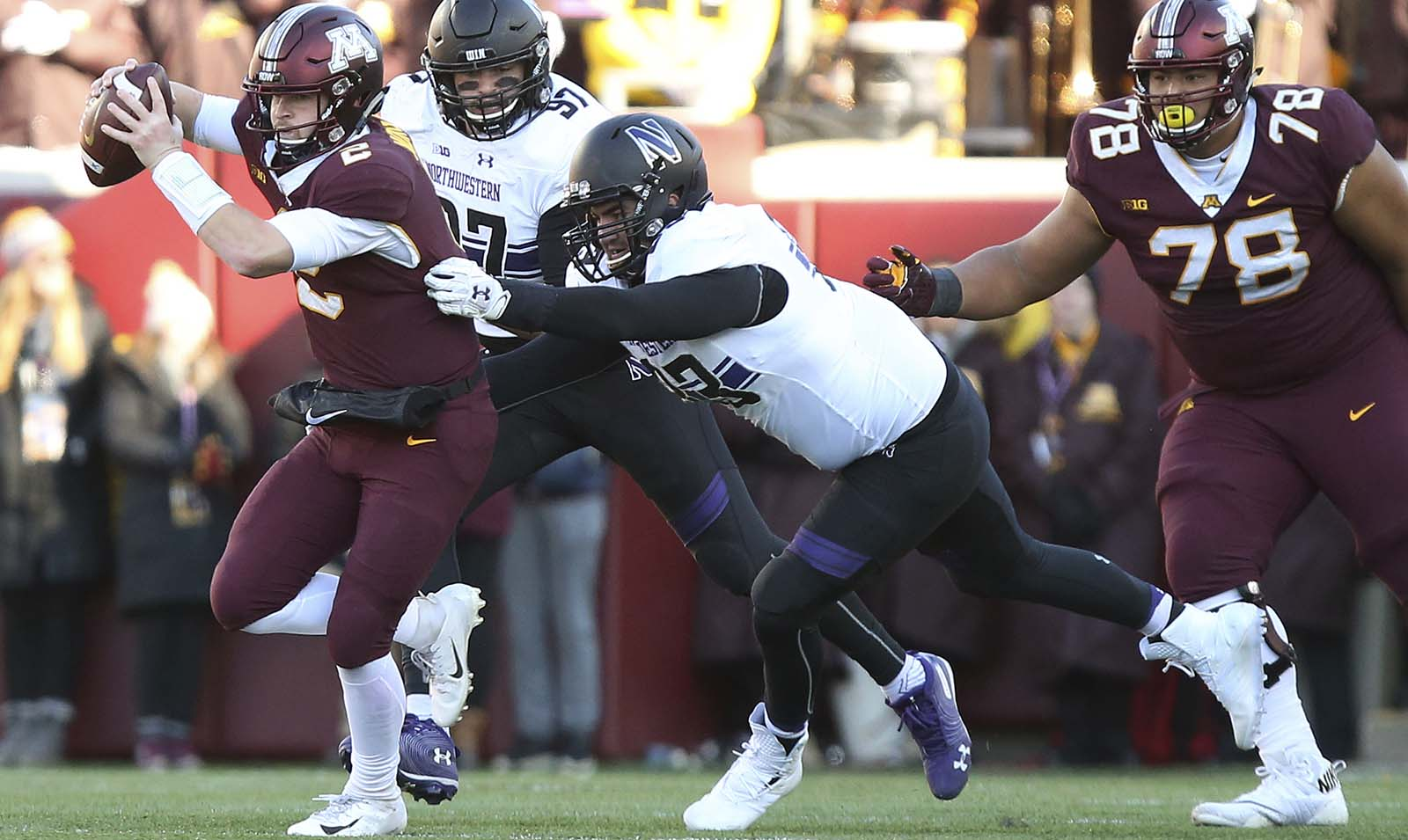 Minnesota quarterback Tanner Morgan, left, avoids a sack by Northwestern's Ben Oxley during an NCAA college football game Saturday, Nov. 17, 2018, in Minneapolis. Northwestern won 24-14. (AP Photo/Stacy Bengs)