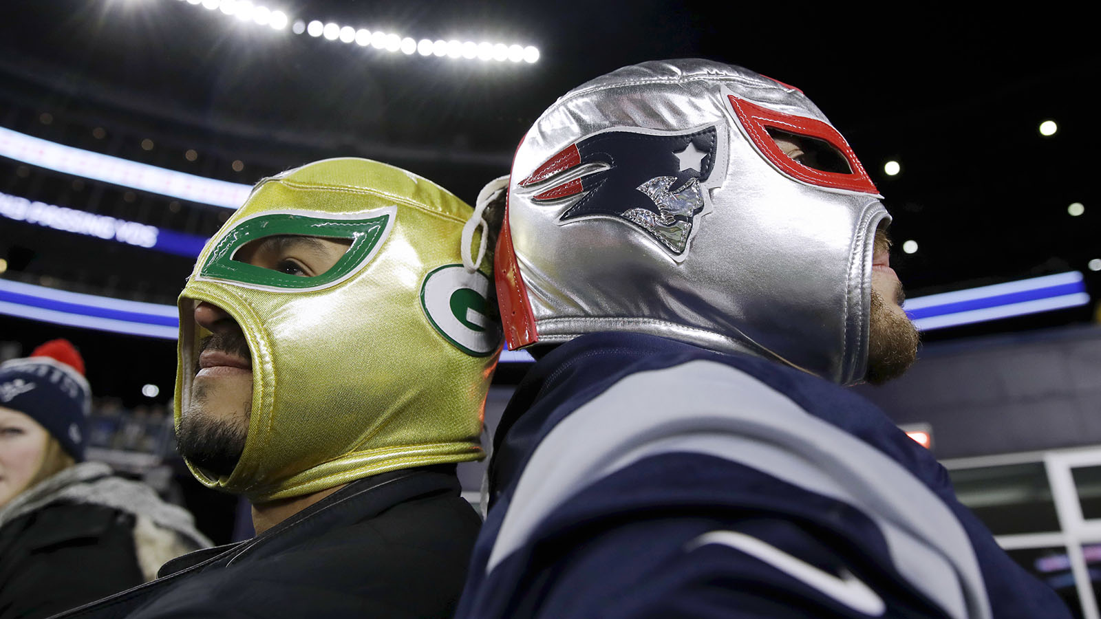 A Green Bay Packers fan, left, and a New England Patriots fan stand back to back before an NFL football game between the Patriots and the Packers, Sunday, Nov. 4, 2018, in Foxborough, Mass. (AP Photo/Charles Krupa)