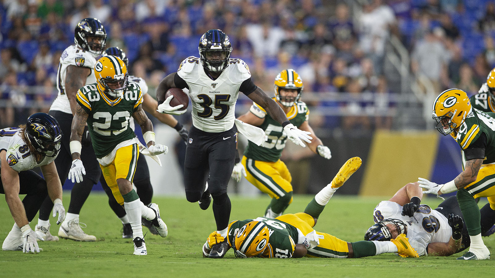 Aug 15, 2019; Baltimore, MD, USA; Baltimore Ravens running back Gus Edwards (35) breaks Green Bay Packers strong safety Adrian Amos (31) arm tackle during the first quarter as cornerback Jaire Alexander (23)  defends at M&T Bank Stadium. Mandatory Credit: Tommy Gilligan-USA TODAY Sports