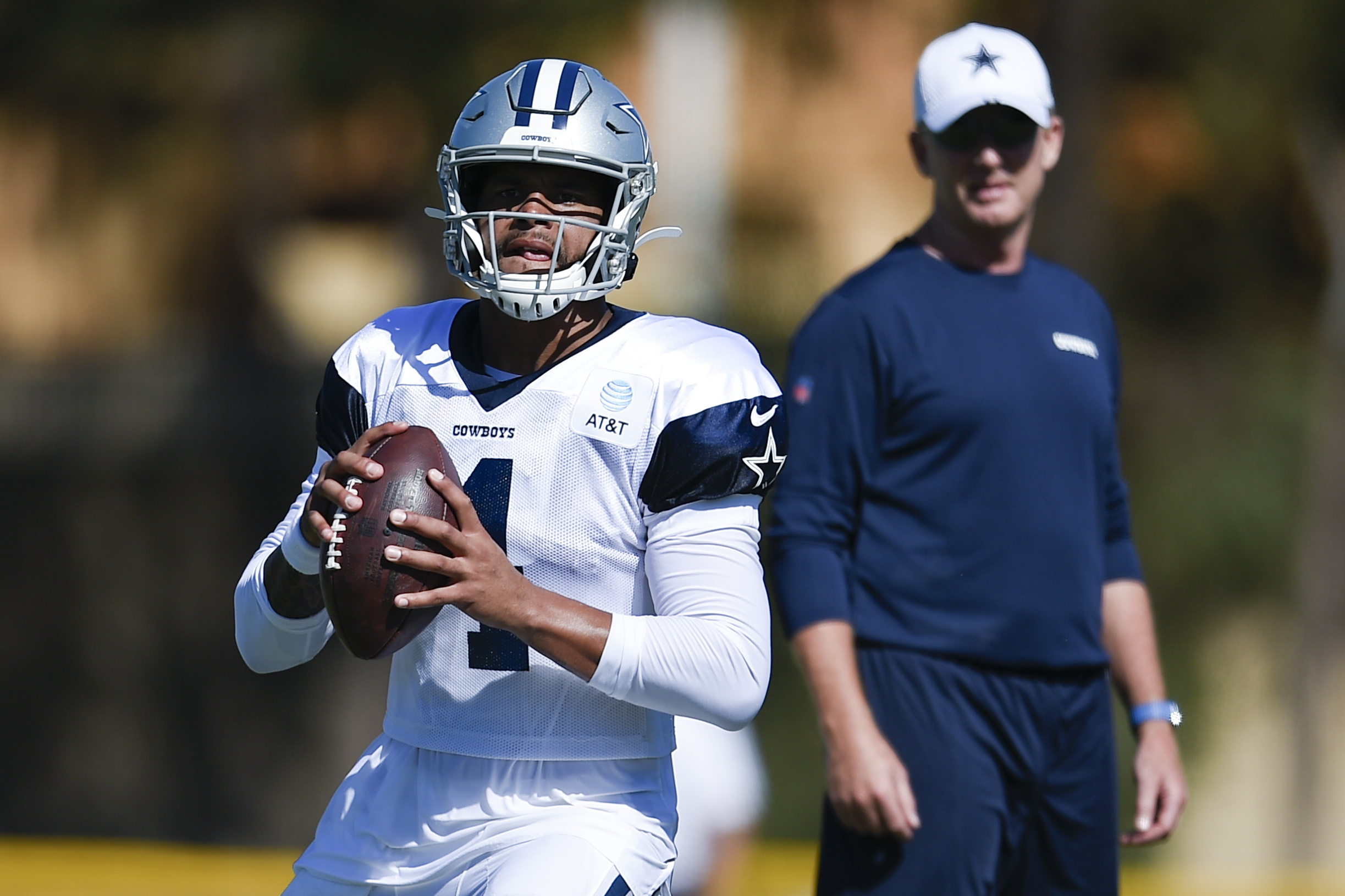 Aug 1, 2019; Oxnard, CA, USA; Dallas Cowboys quarterback Dak Prescott (4) looks to pass as head coach Jason Garrett watches during training camp at Marriott Residence Inn at River Ridge. Mandatory Credit: Kelvin Kuo-USA TODAY Sports