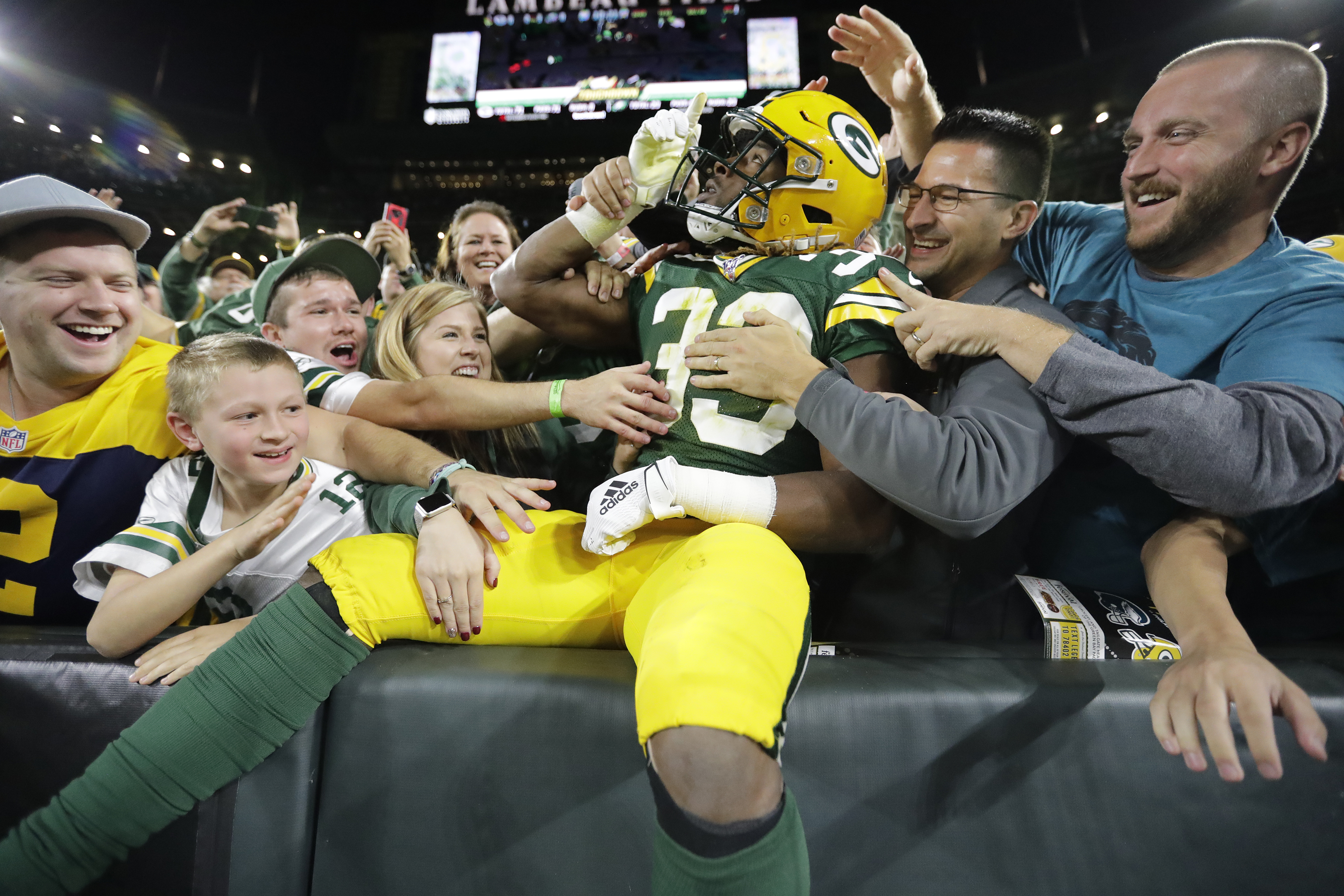 Sept 26, 2019; Green Bay, WI, USA; Green Bay Packers running back Aaron Jones (33) points to the sky as he celebrates scoring a touchdown with fans against Philadelphia Eagles during the first quarter at Lambeau Field. Mandatory Credit: Dan Powers/USA TODAY NETWORK-Wisconsin via USA Today Sports