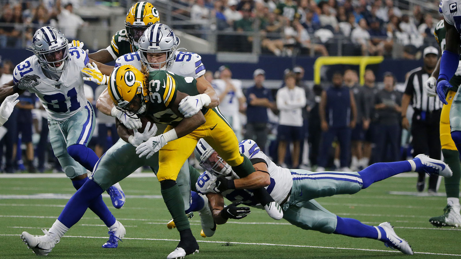 Green Bay Packers running back Aaron Jones (33) carries Dallas Cowboys outside linebacker Leighton Vander Esch (55) and strong safety Jeff Heath (38) as he gains extra yardage on a run for a first down in the first half of an NFL football game in Arlington, Texas, Sunday, Oct. 6, 2019. (AP Photo/Michael Ainsworth)