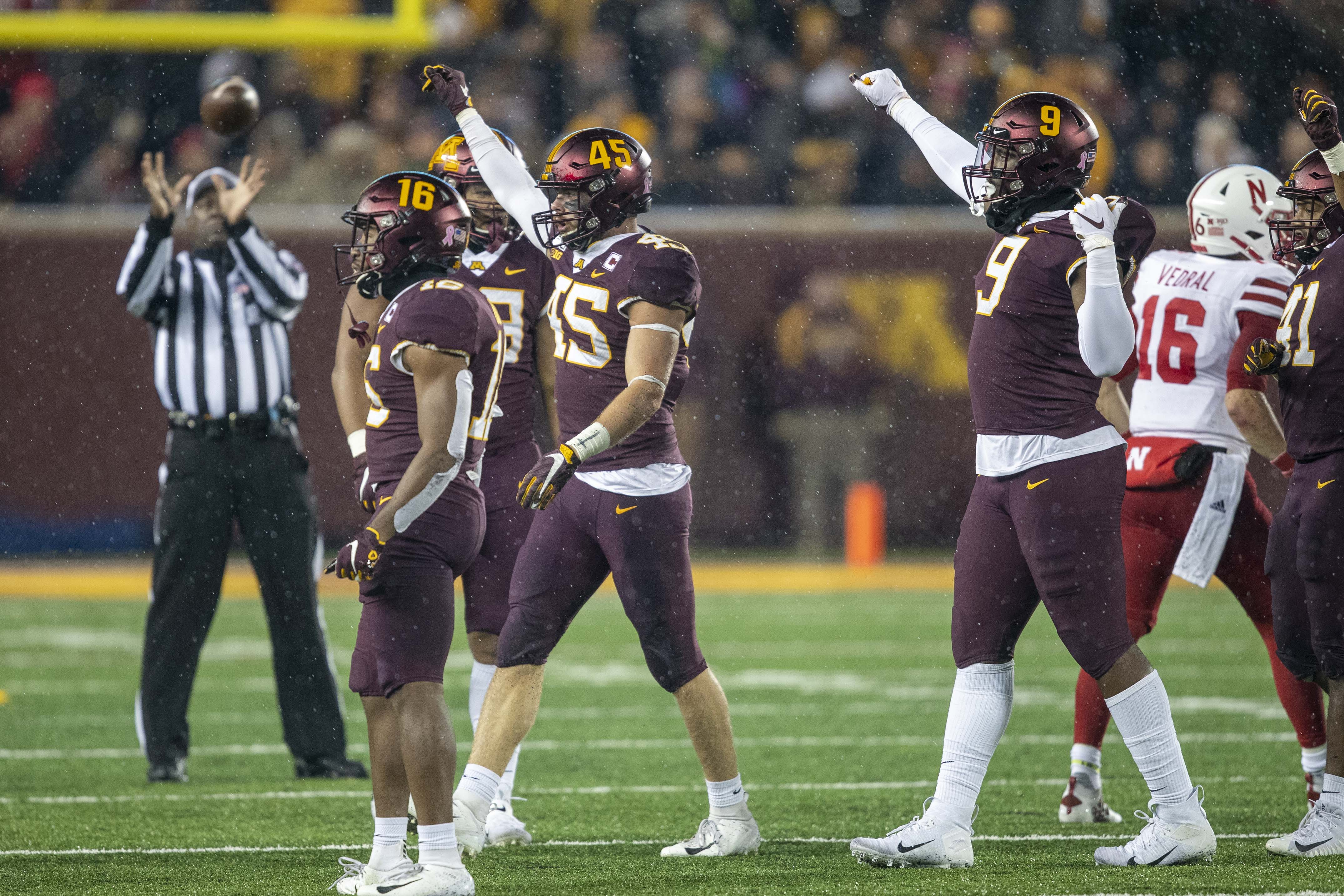 Oct 12, 2019; Minneapolis, MN, USA; Minnesota Golden Gophers linebacker Mariano Sori-Marin (55) defensive lineman Esezi Otomewo (9) holds up their fists after making a a tackle on third down in the first half against the Nebraska Cornhuskers at TCF Bank Stadium. Mandatory Credit: Jesse Johnson-USA TODAY Sports